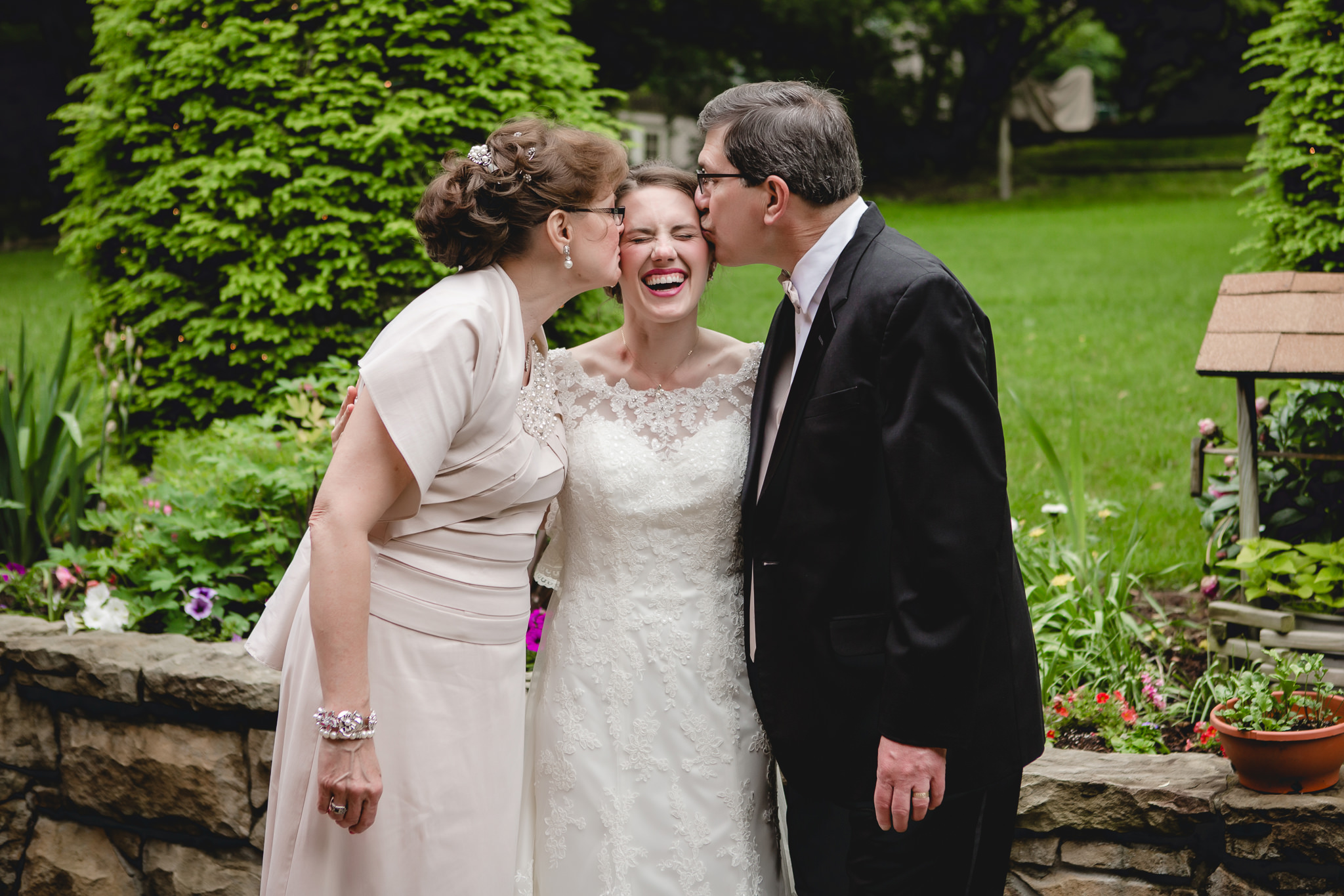 Bride's parents give her kisses before her Shannopin Country Club wedding