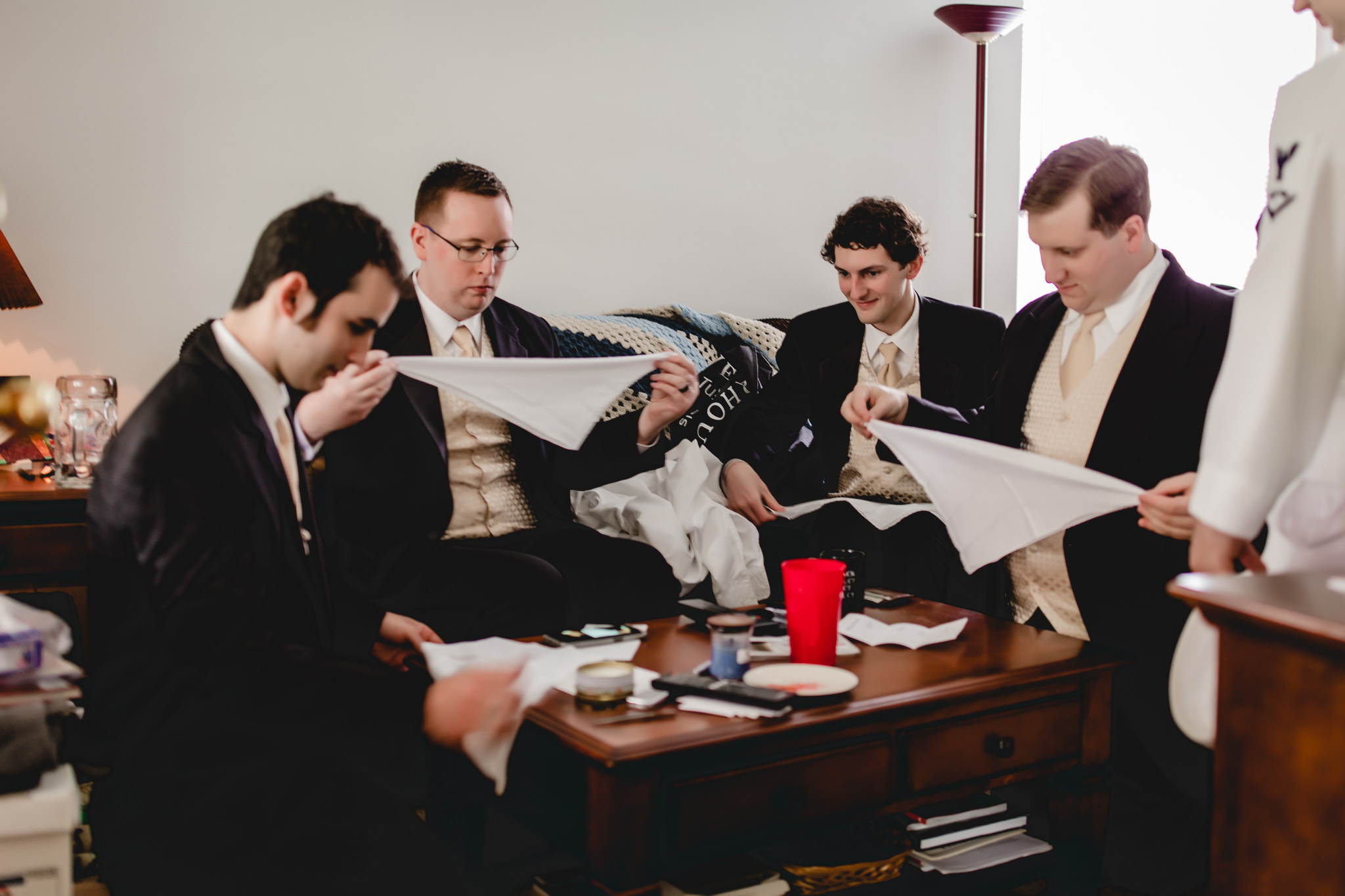 Groomsmen folding pocket squares before Shannopin Country Club wedding