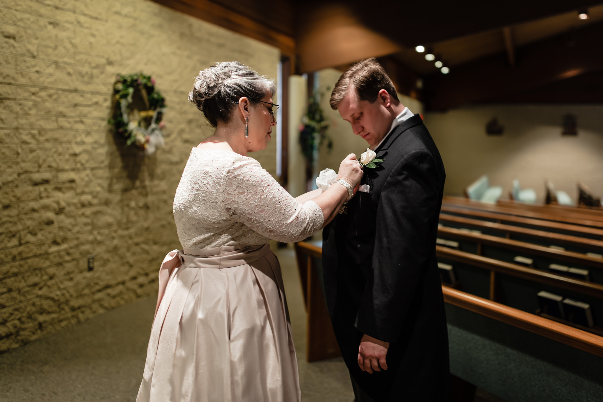 Mother of the groom pins his boutonniere before ceremony at St. John Neumann Church