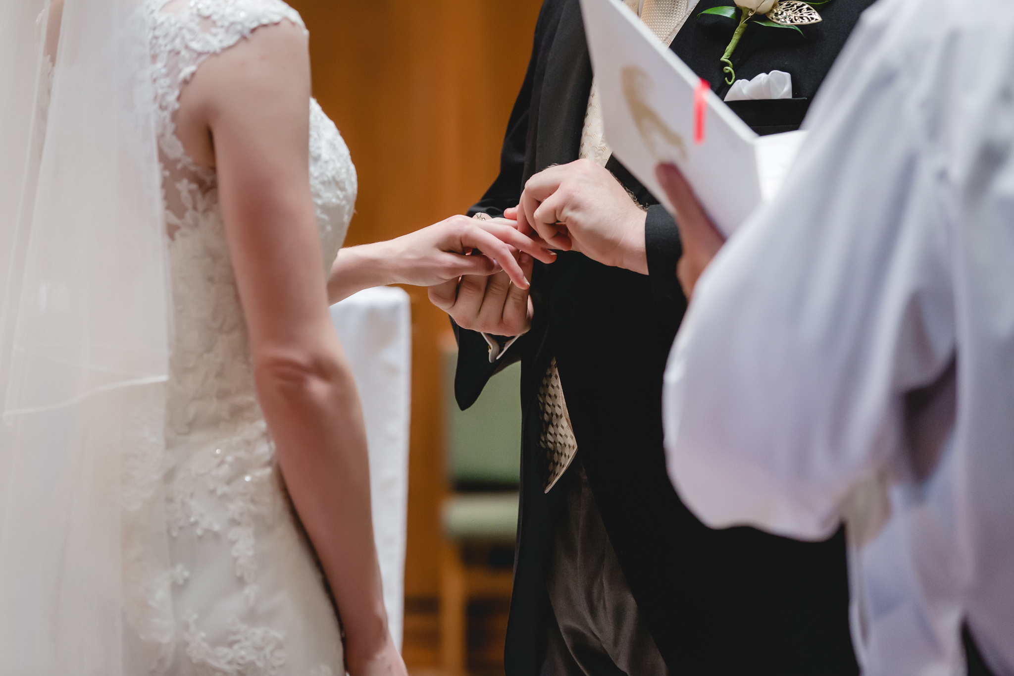 Groom puts ring on bride's finger at St. John Neumann Church in Pittsburgh PA