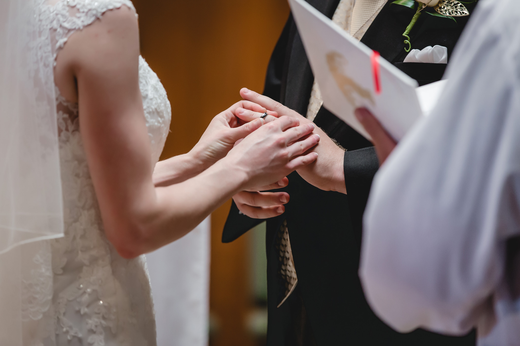 Bride puts ring on groom's finger at St. John Neumann Church in Pittsburgh PA