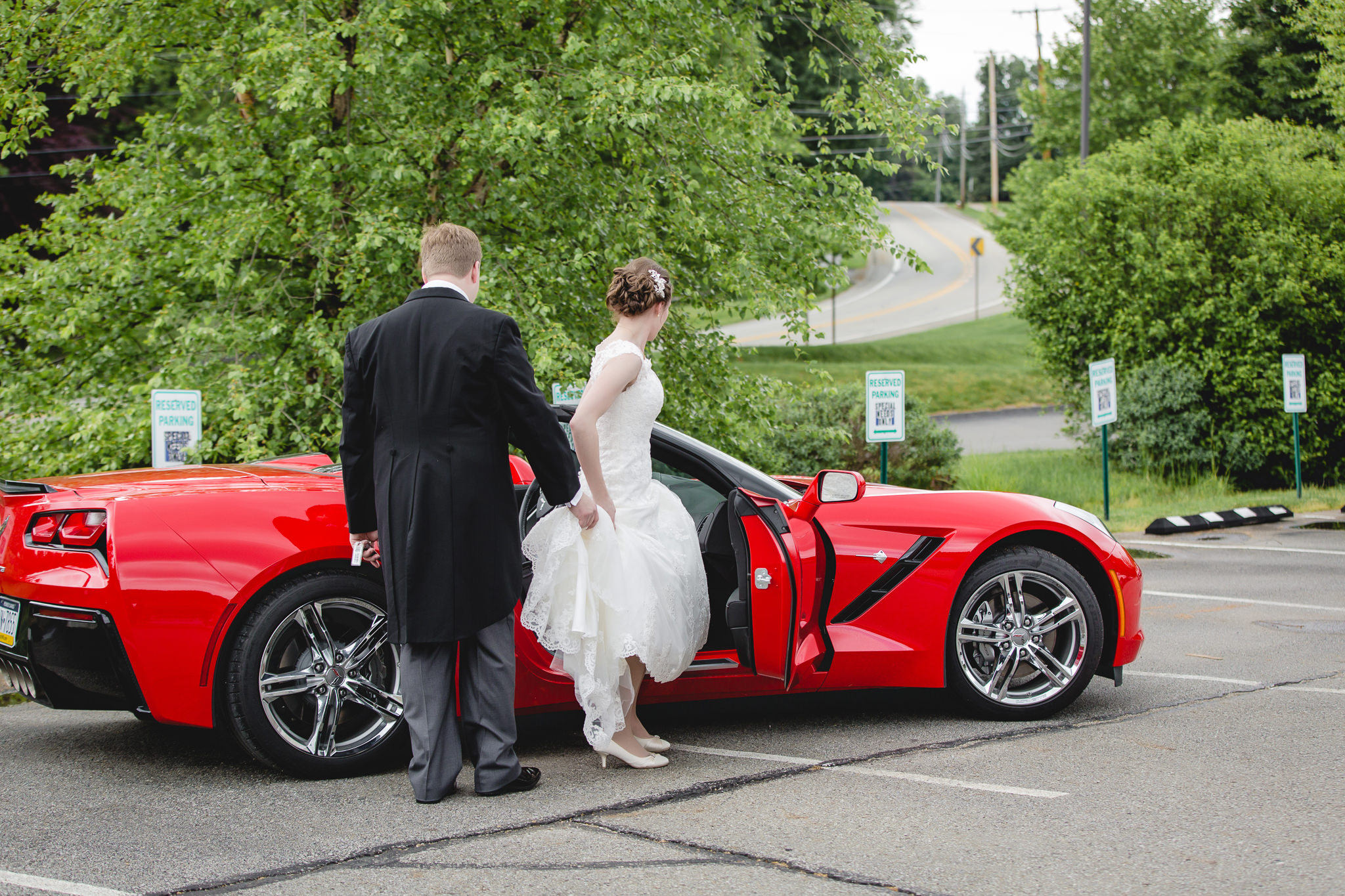 Groom helps bride into red Corvette at St. John Neumann Church in Pittsburgh PA