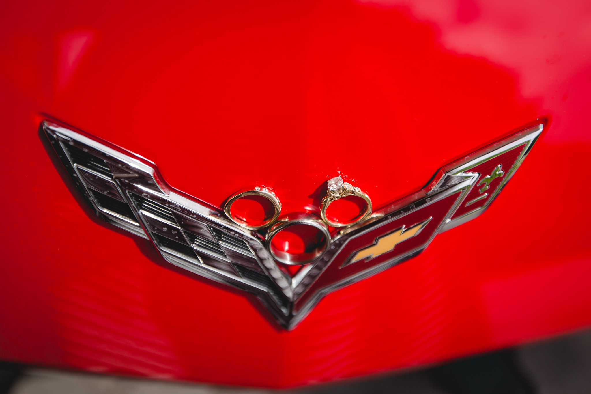 Wedding rings on red Corvette logo at Shannopin Country Club