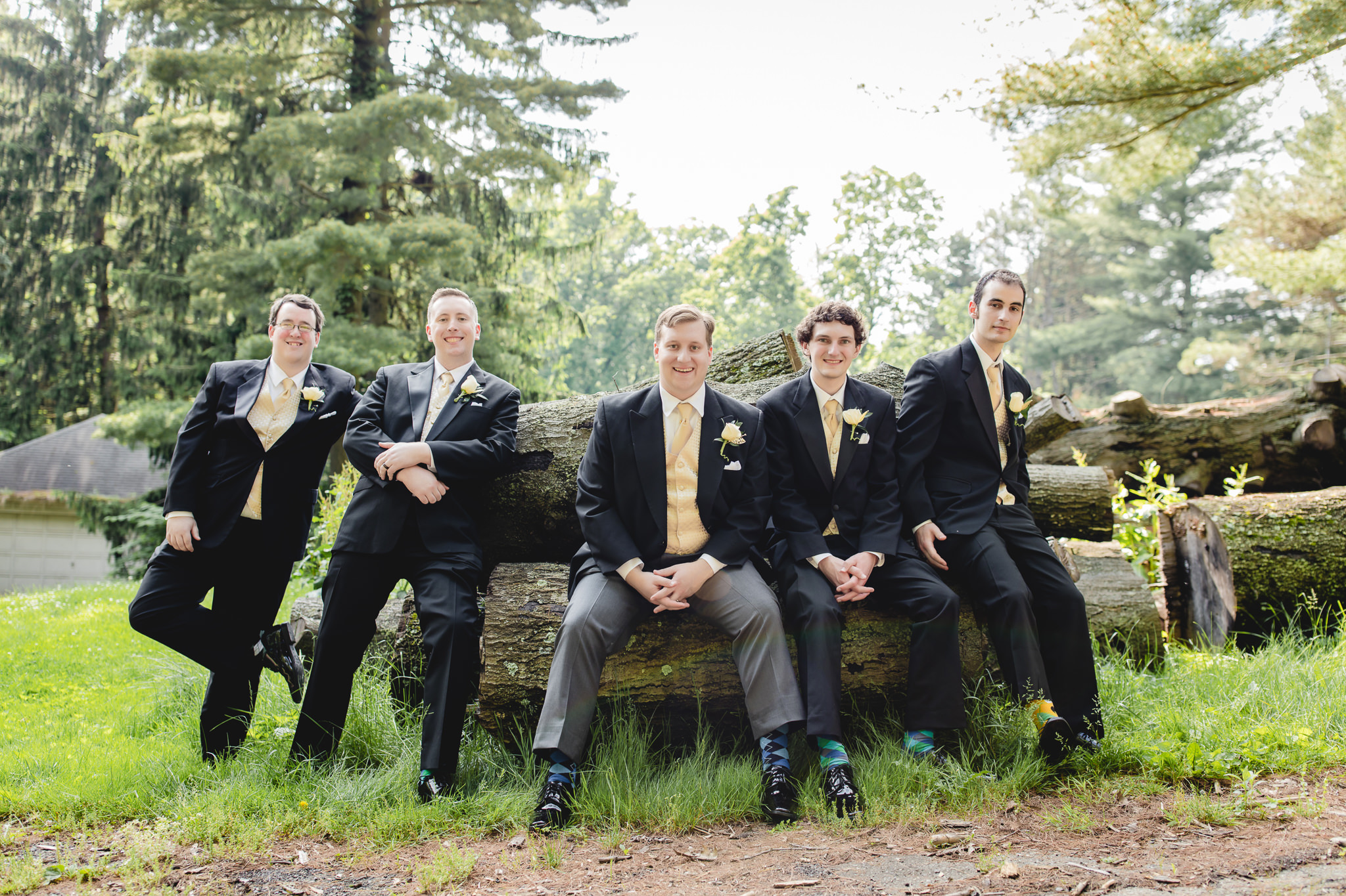 Groomsmen on logs at Shannopin Country Club wedding