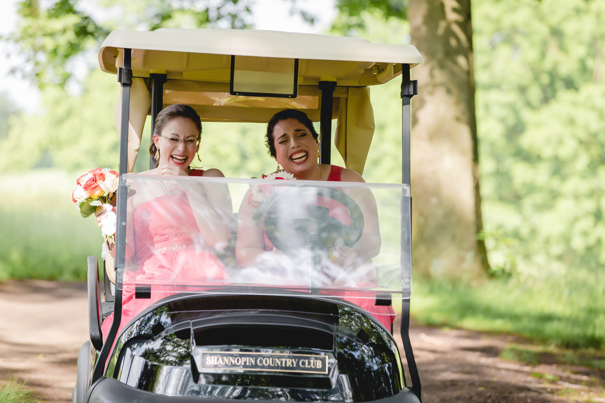 Bridesmaids laughing in golf cart at Shannopin Country Club wedding