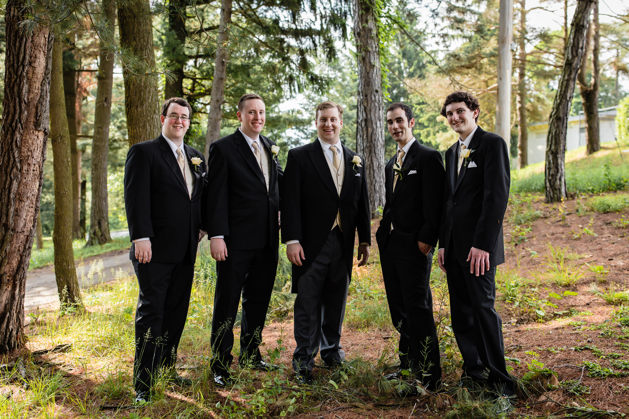 Groomsmen pose in woods by Shannopin Country Club