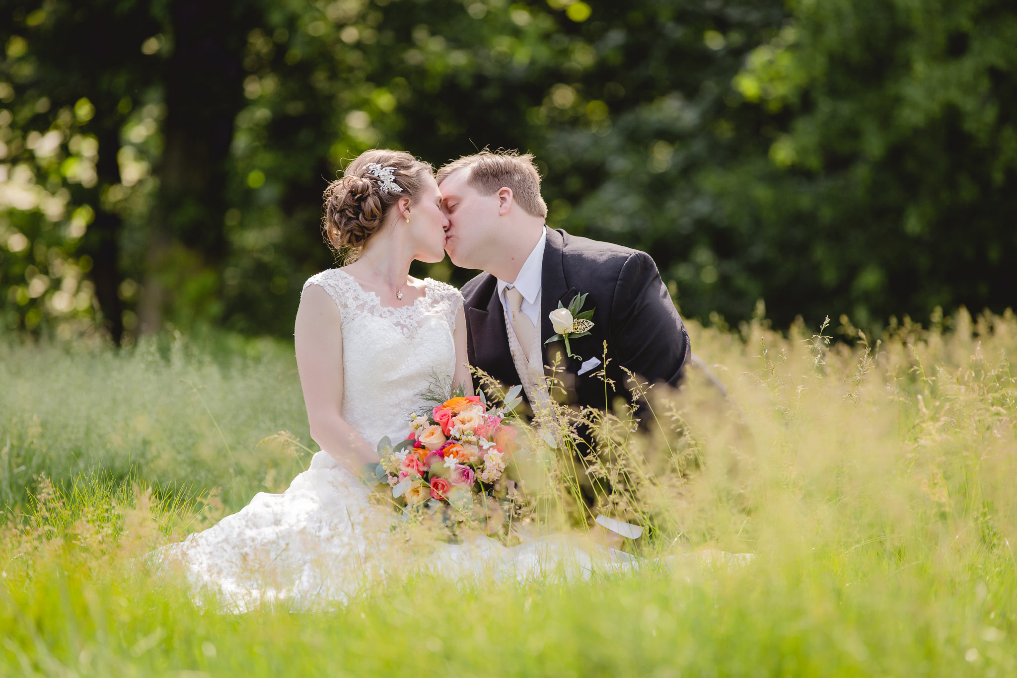 Bride & groom kissing in a field at Shannopin Country Club