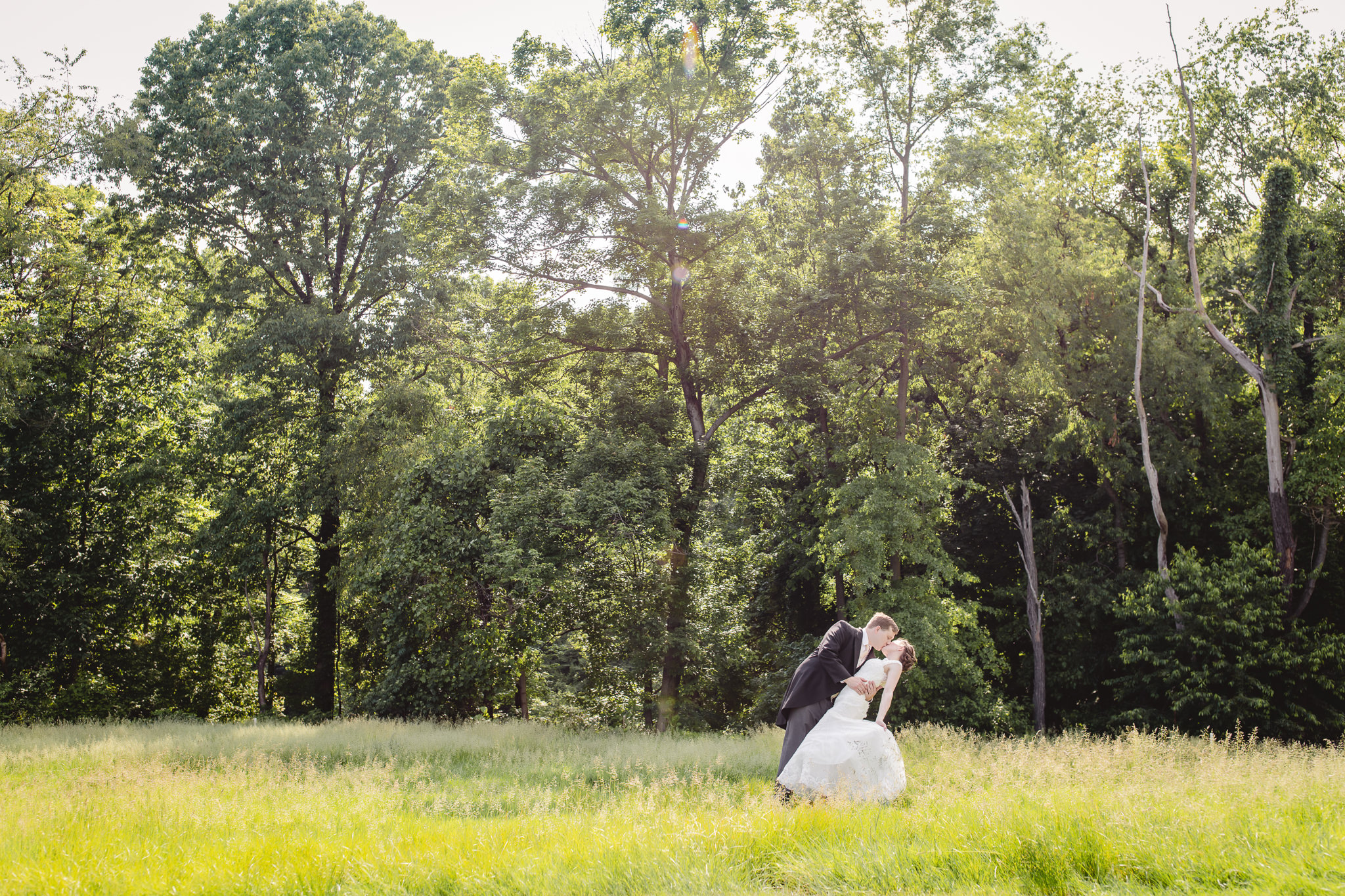Groom dips his bride in a field at Shannopin Country Club