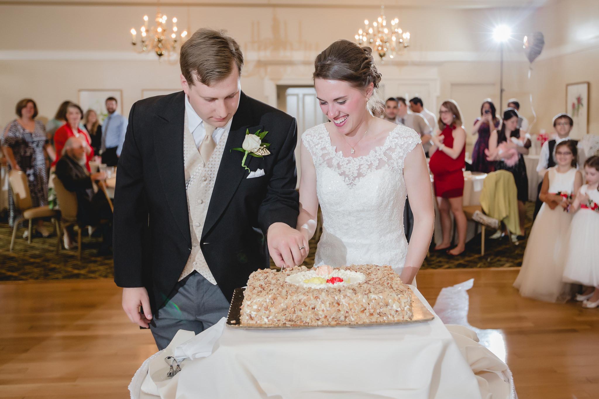 Newlyweds cutting their cake at Shannopin Country Club wedding reception