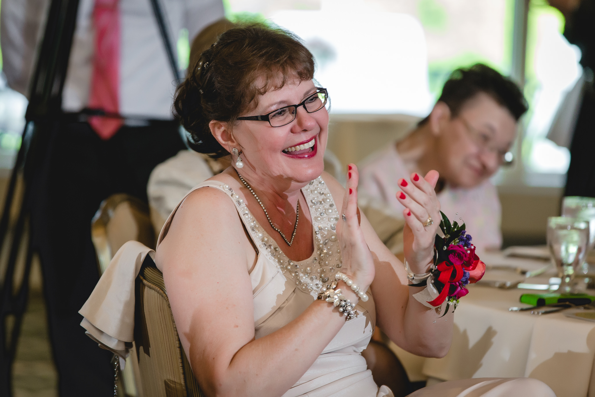 Mother of the bride laughs during toasts at Shannopin Country Club wedding reception
