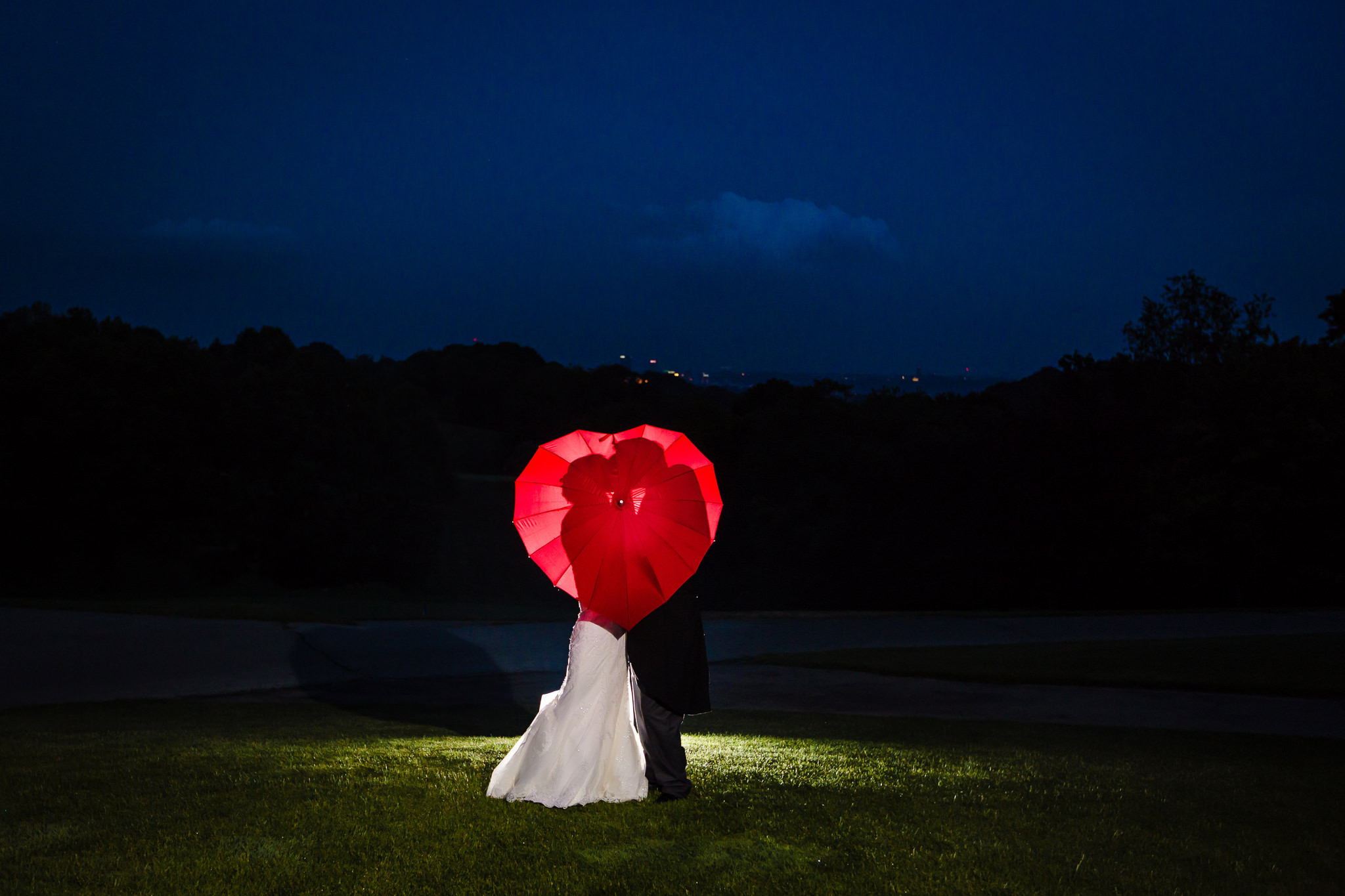 Night portrait of bride & groom with heart-shaped umbrella at Shannopin Country Club