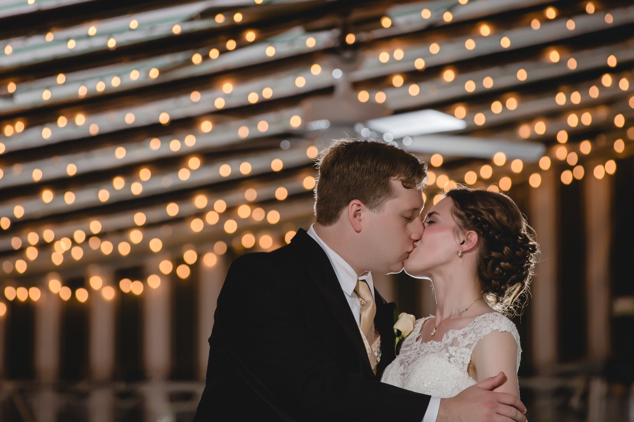 Bride & groom under string lights at night at Shannopin Country Club