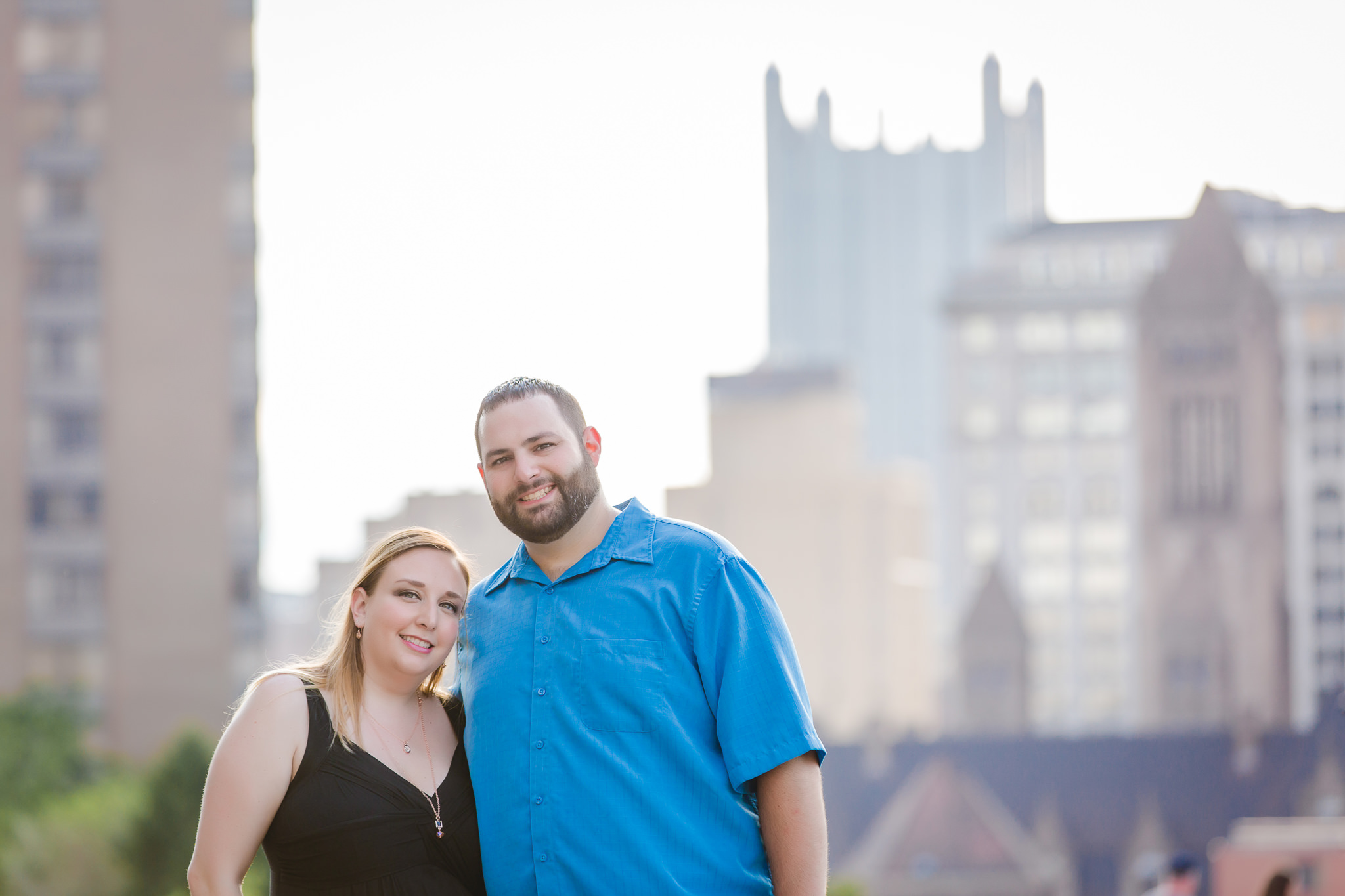 Engaged couple smile for the camera with Pittsburgh's iconic PPG building in the background