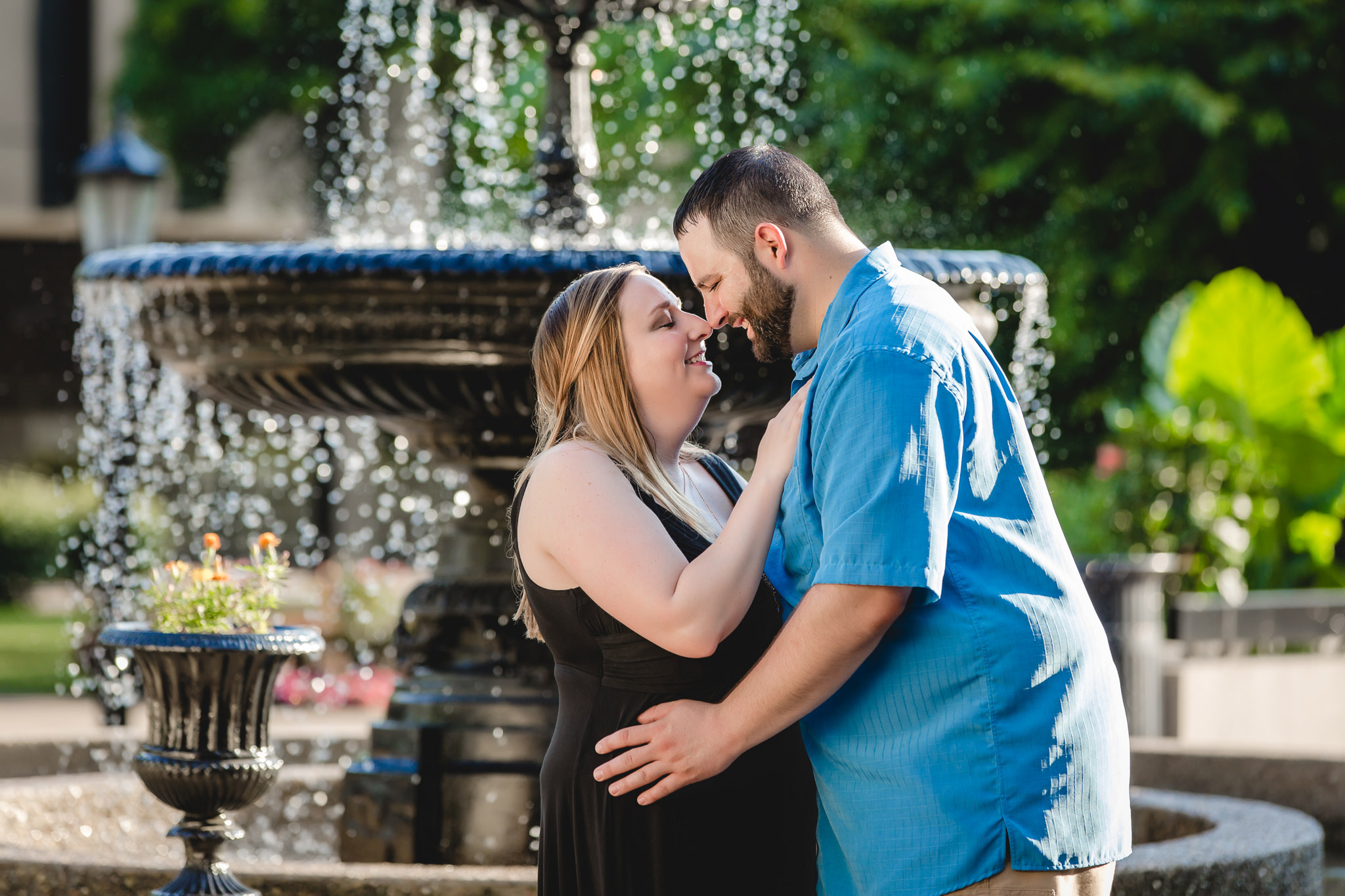 Duquesne University alumni nuzzle noses in front of a fountain during their engagement session on campus
