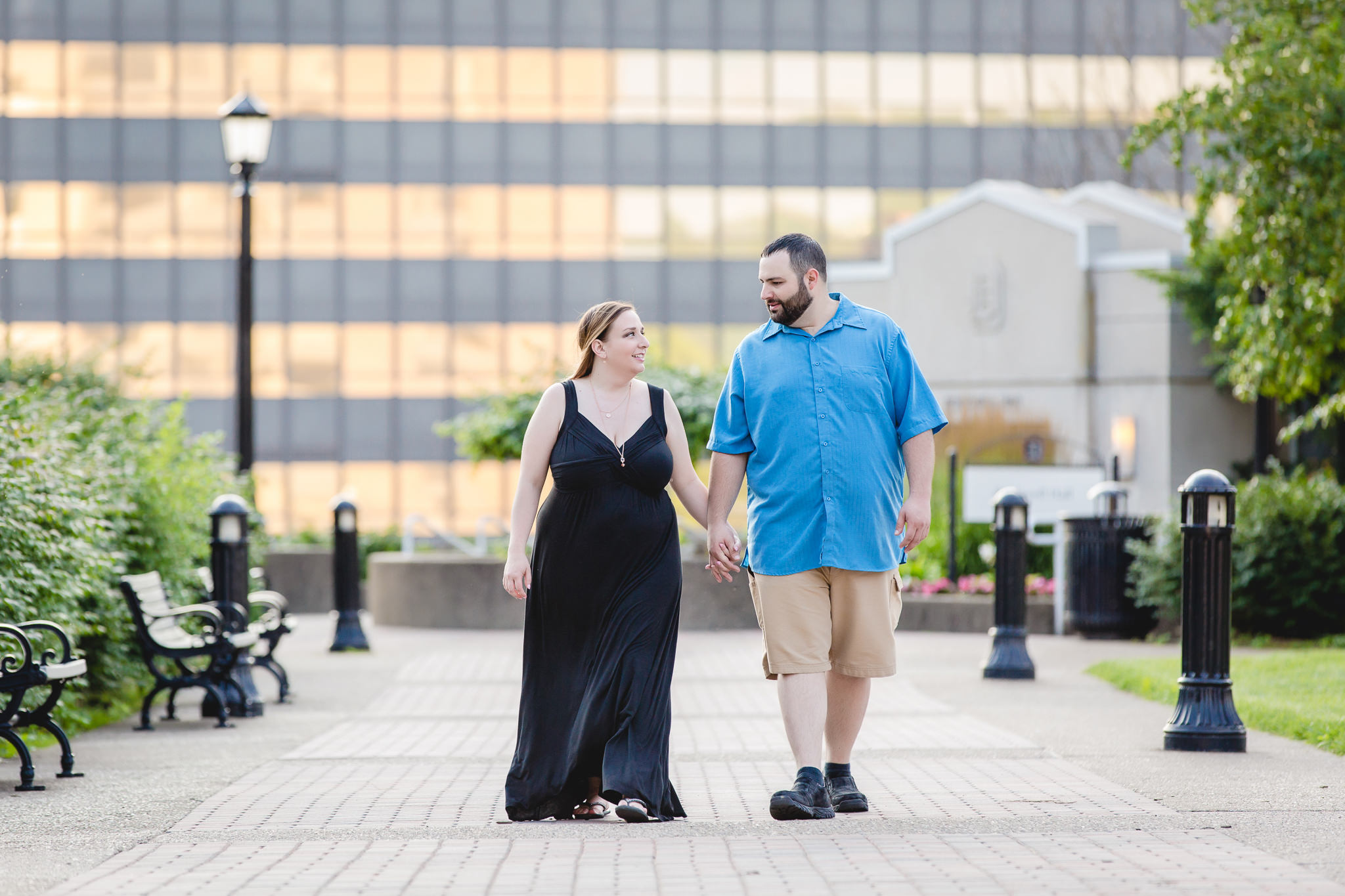 Engaged couple walks near Rockwell Hall during their engagement session at Duquesne University