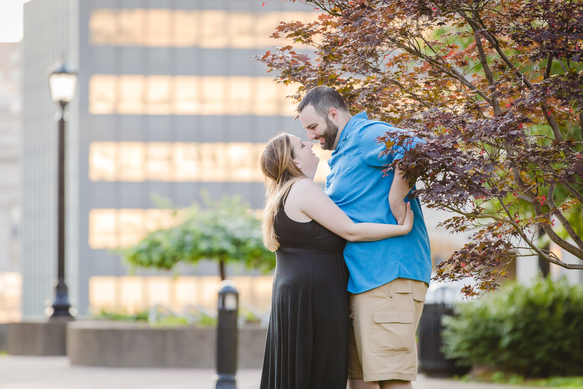 Engaged couple playfully snuggles during their engagement session on Duquesne's campus