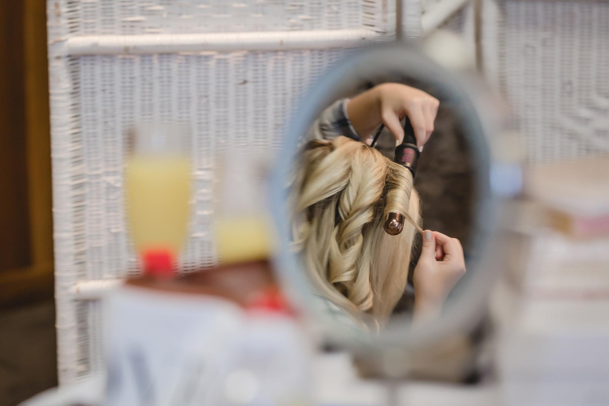 Bridesmaid curls her hair before a wedding ceremony at Hidden Valley Resort