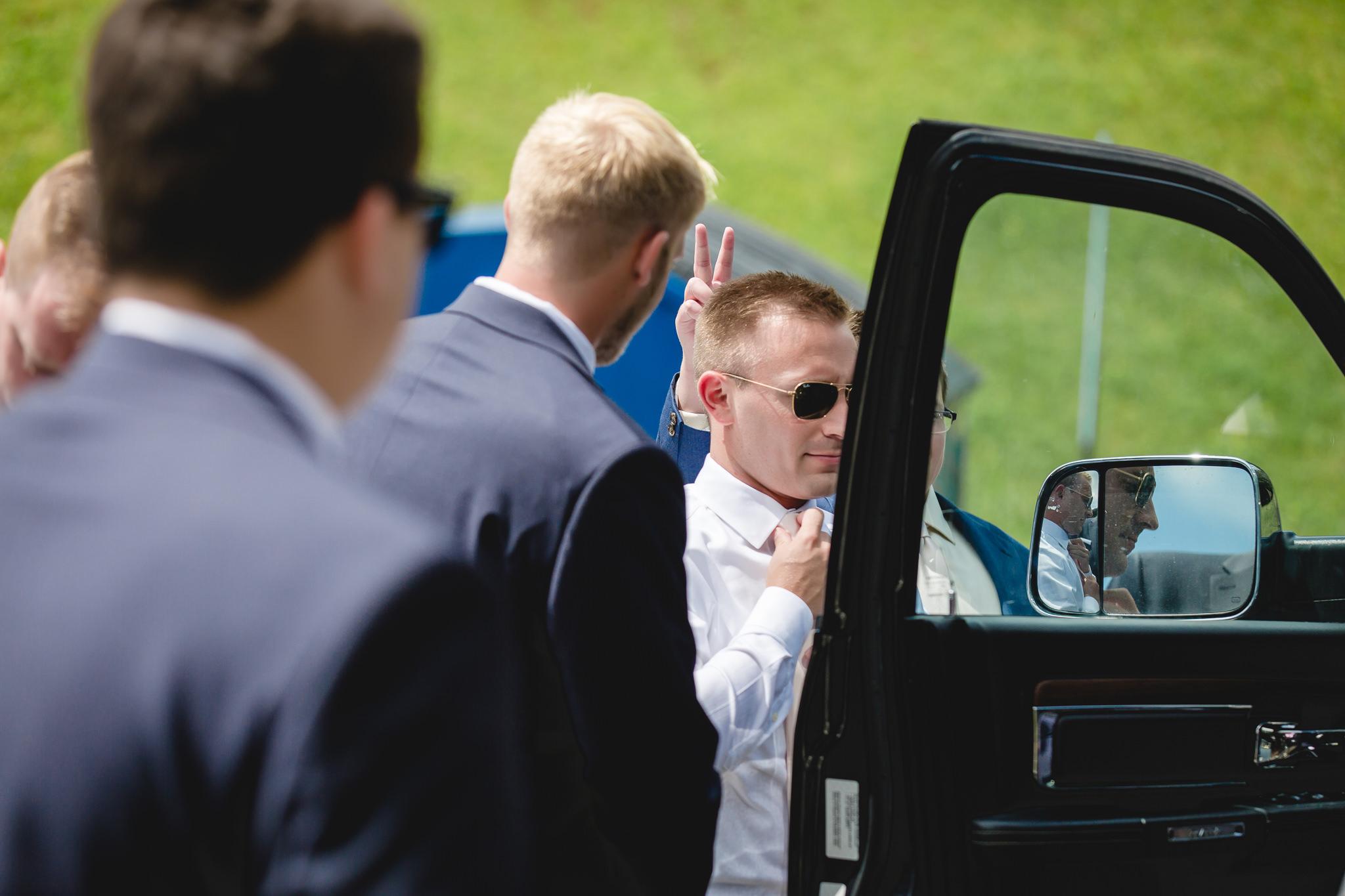 Groom fixes his tie in a car window at Hidden Valley Resort