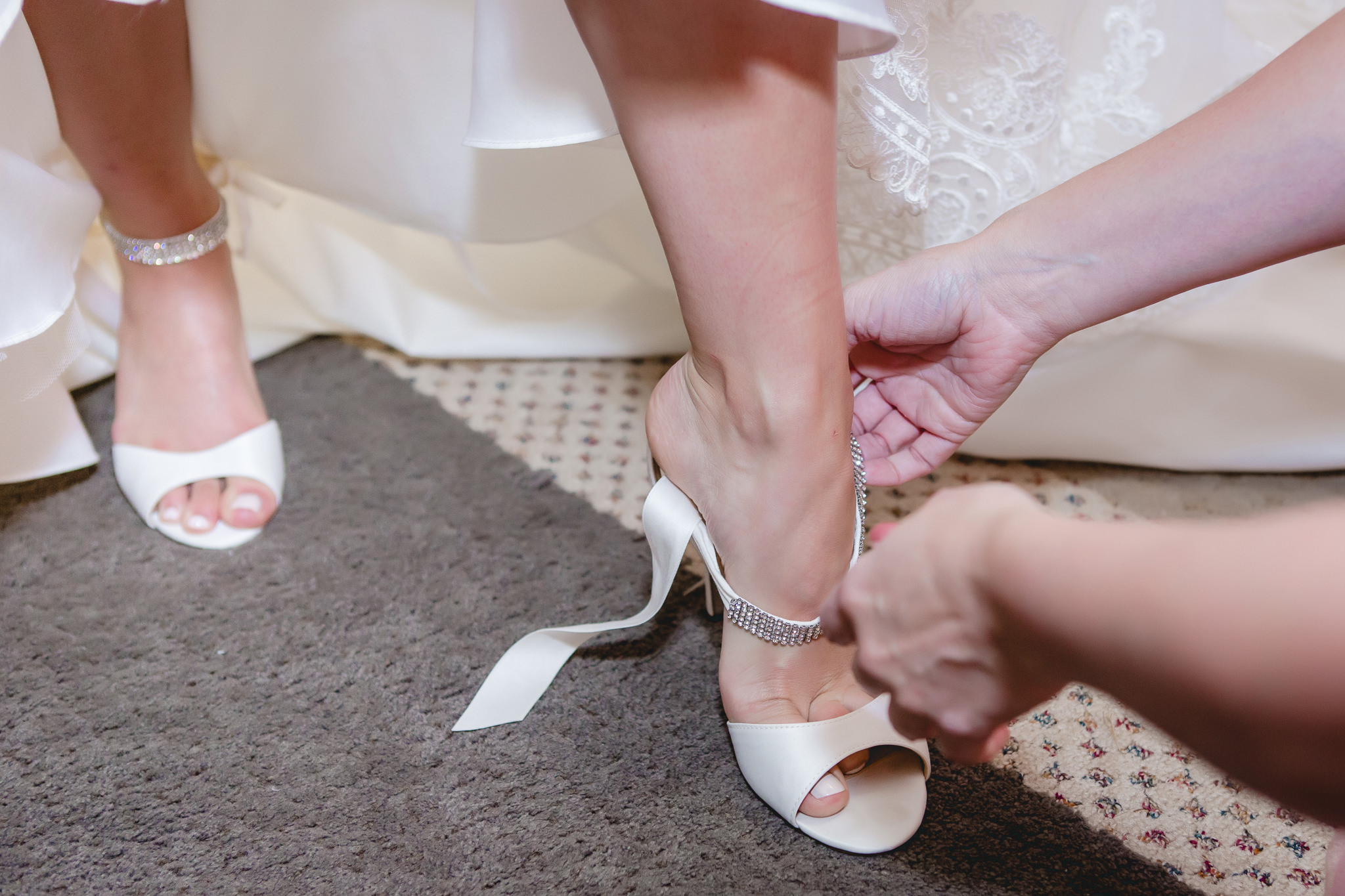 Mother of the bride helps her daughter into her wedding shoes