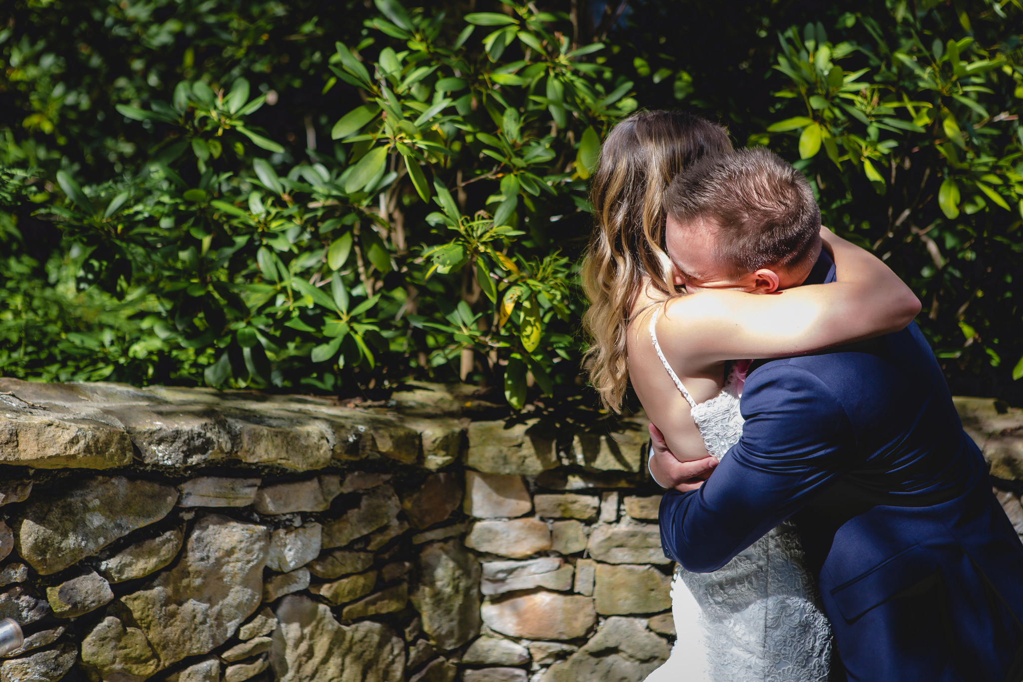 Groom embraces his bride during their first look at Hidden Valley Resort