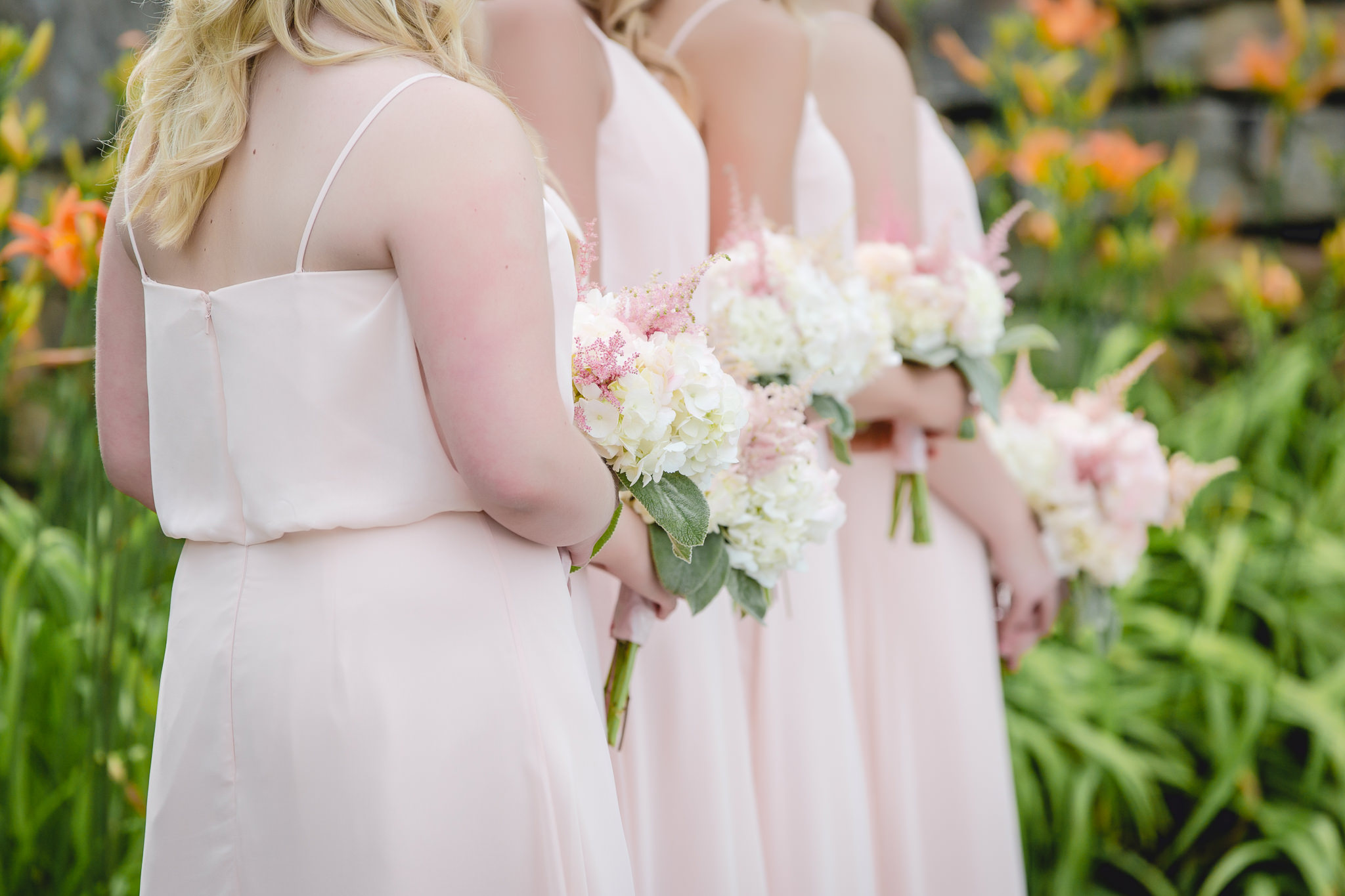 Bridesmaids hold hydrangea bouquets at an outdoor wedding ceremony