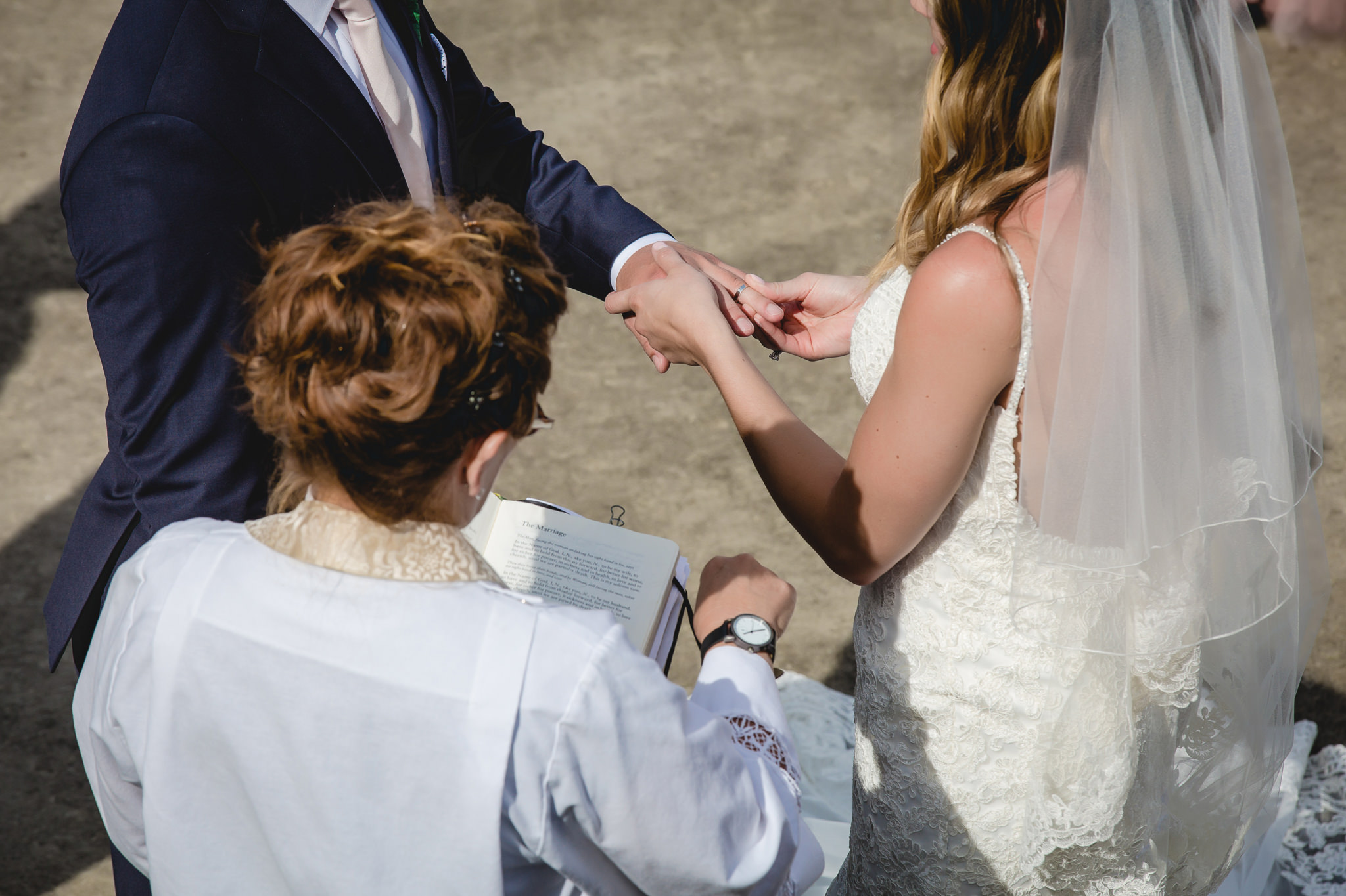 Bride places the ring on her groom's finger at Hidden Valley Resort
