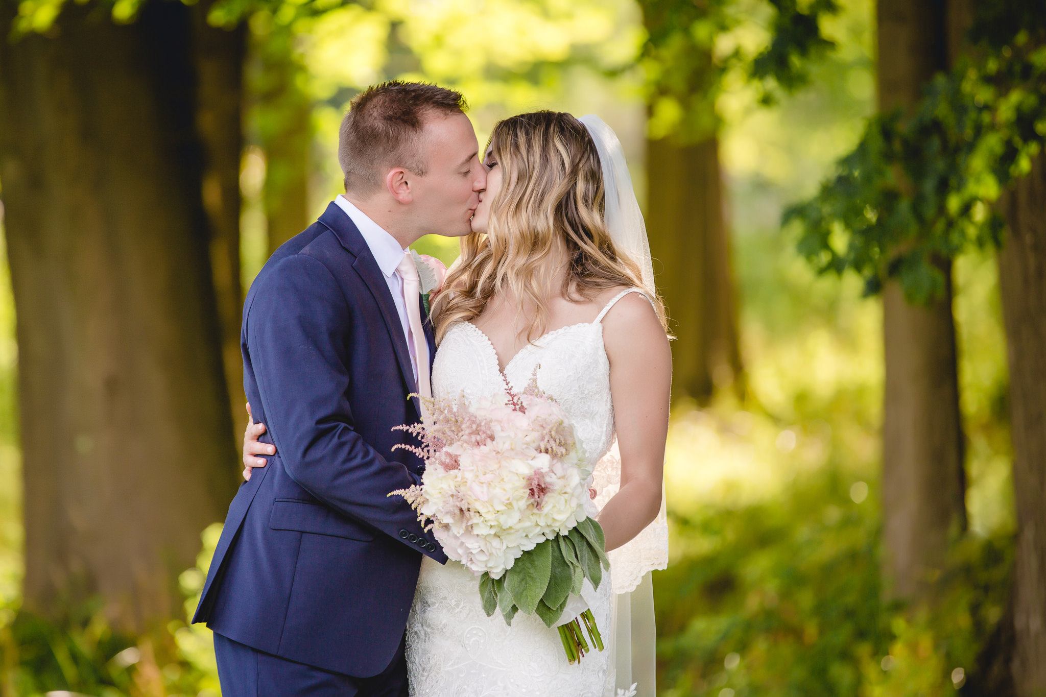 Newlyweds kiss during portraits in a wooded area at Hidden Valley Resort