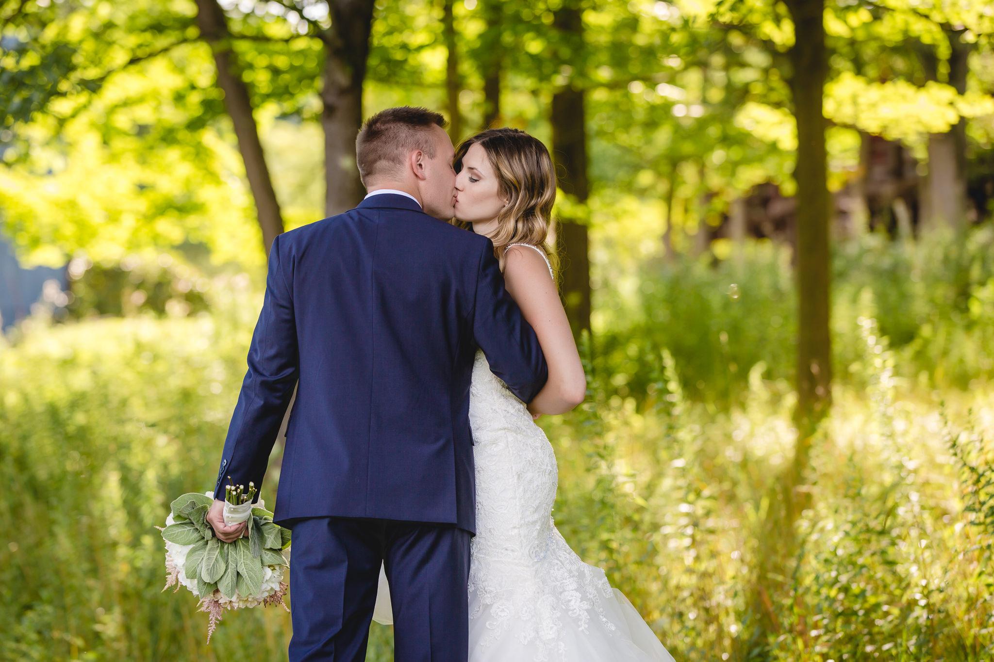 Groom kisses his bride in the woods at Hidden Valley Resort
