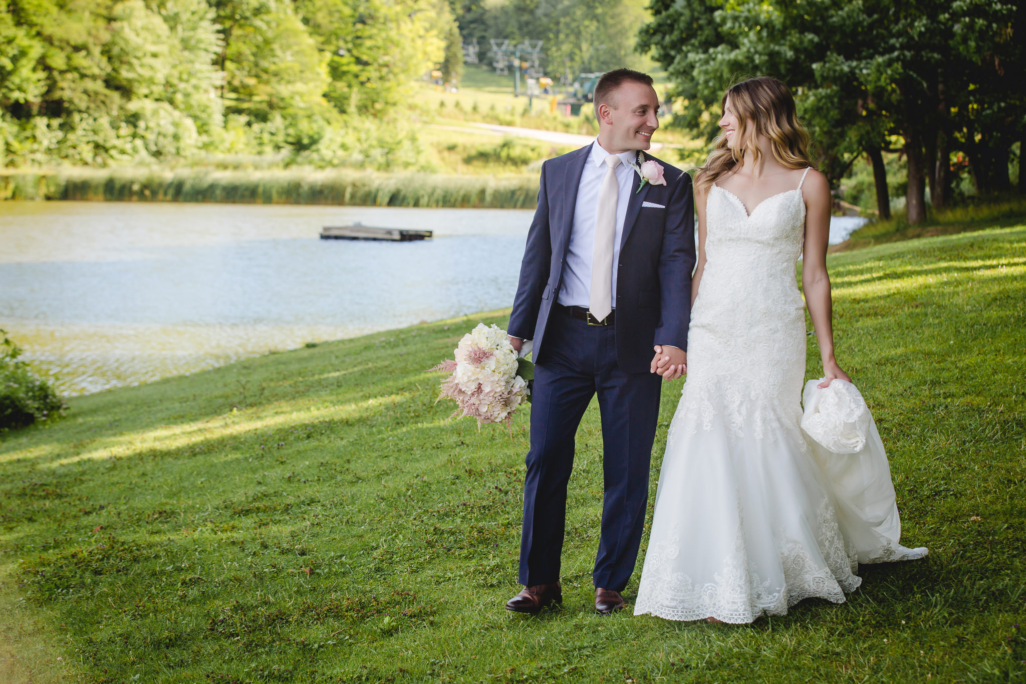 Bride and groom walk by a pond at Hidden Valley Resort