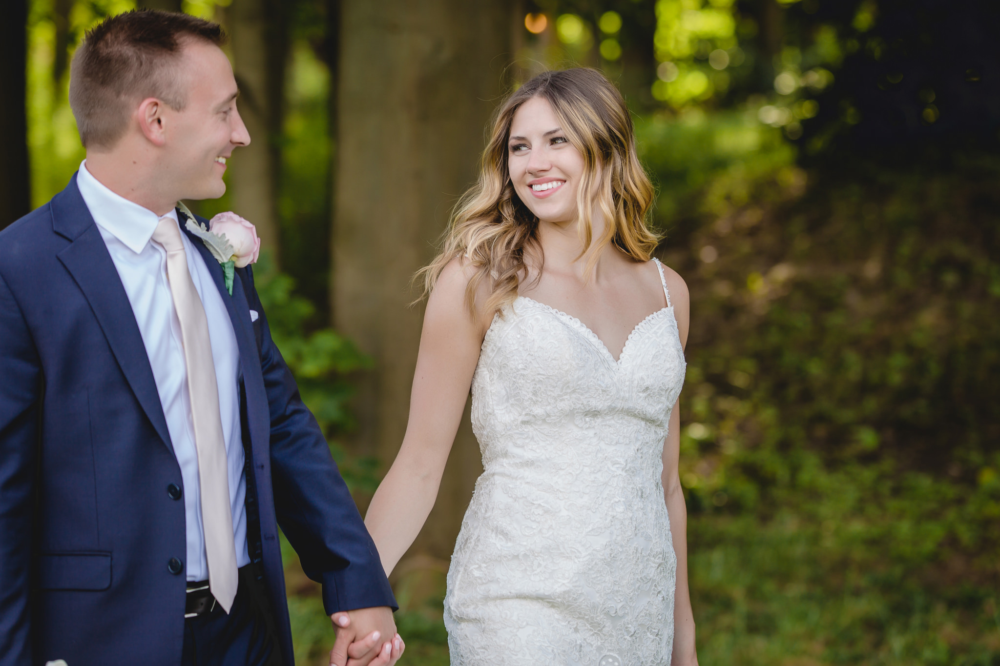 Bride and groom stroll through the woods at Hidden Valley Resort