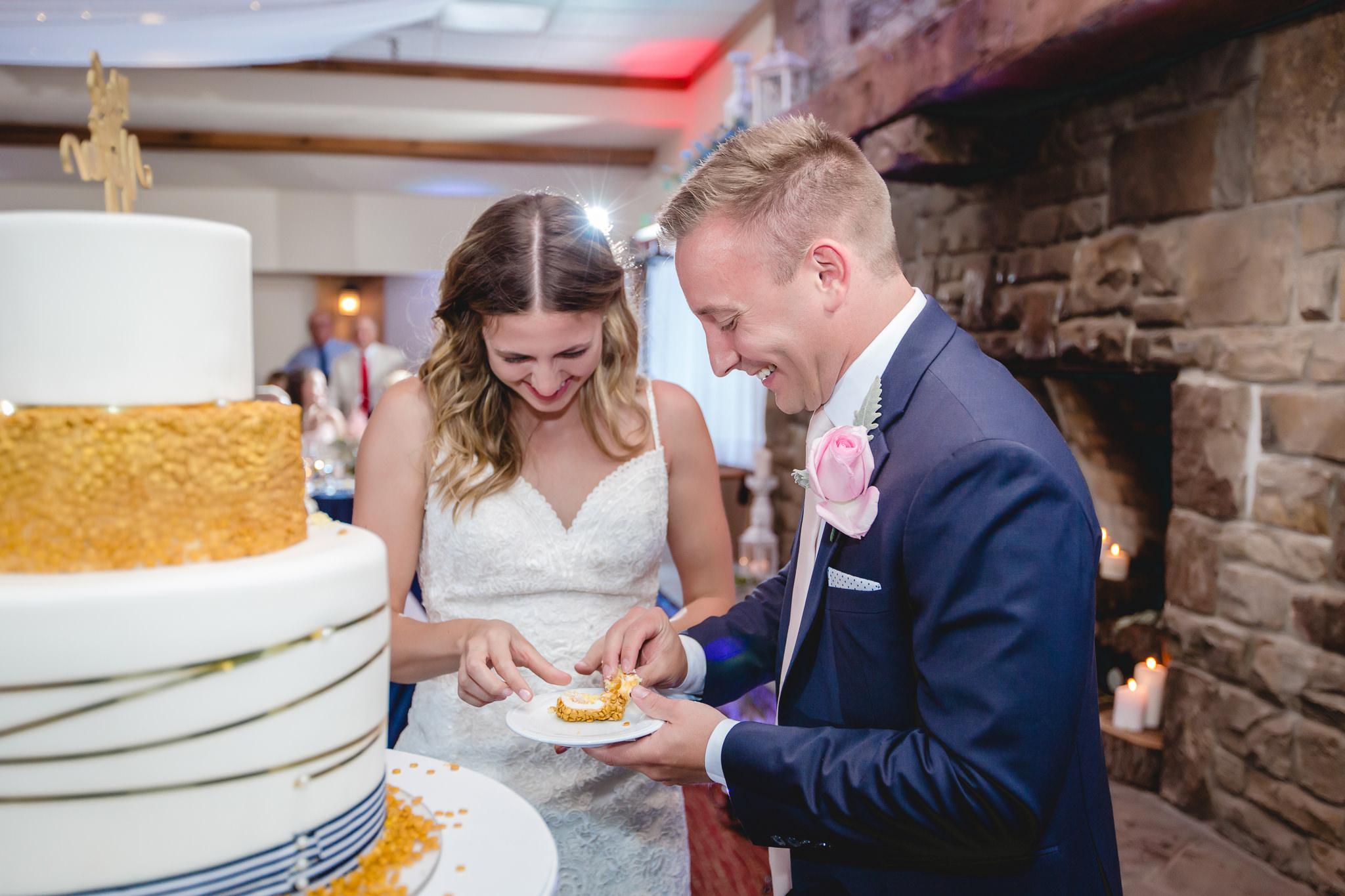 Newlyweds laugh during cake cutting at Hidden Valley Resort wedding reception