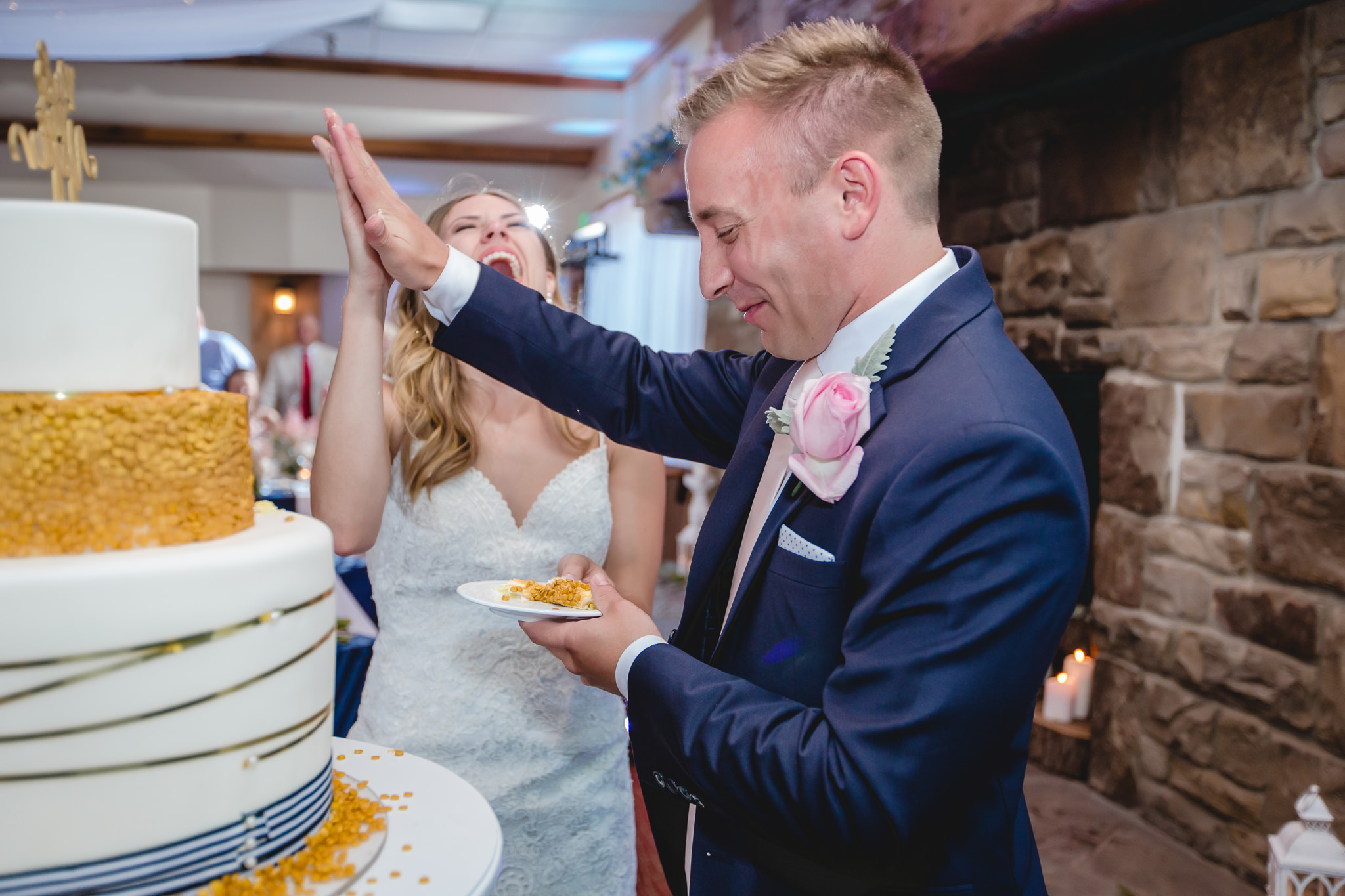 Bride & groom high five after cutting the cake