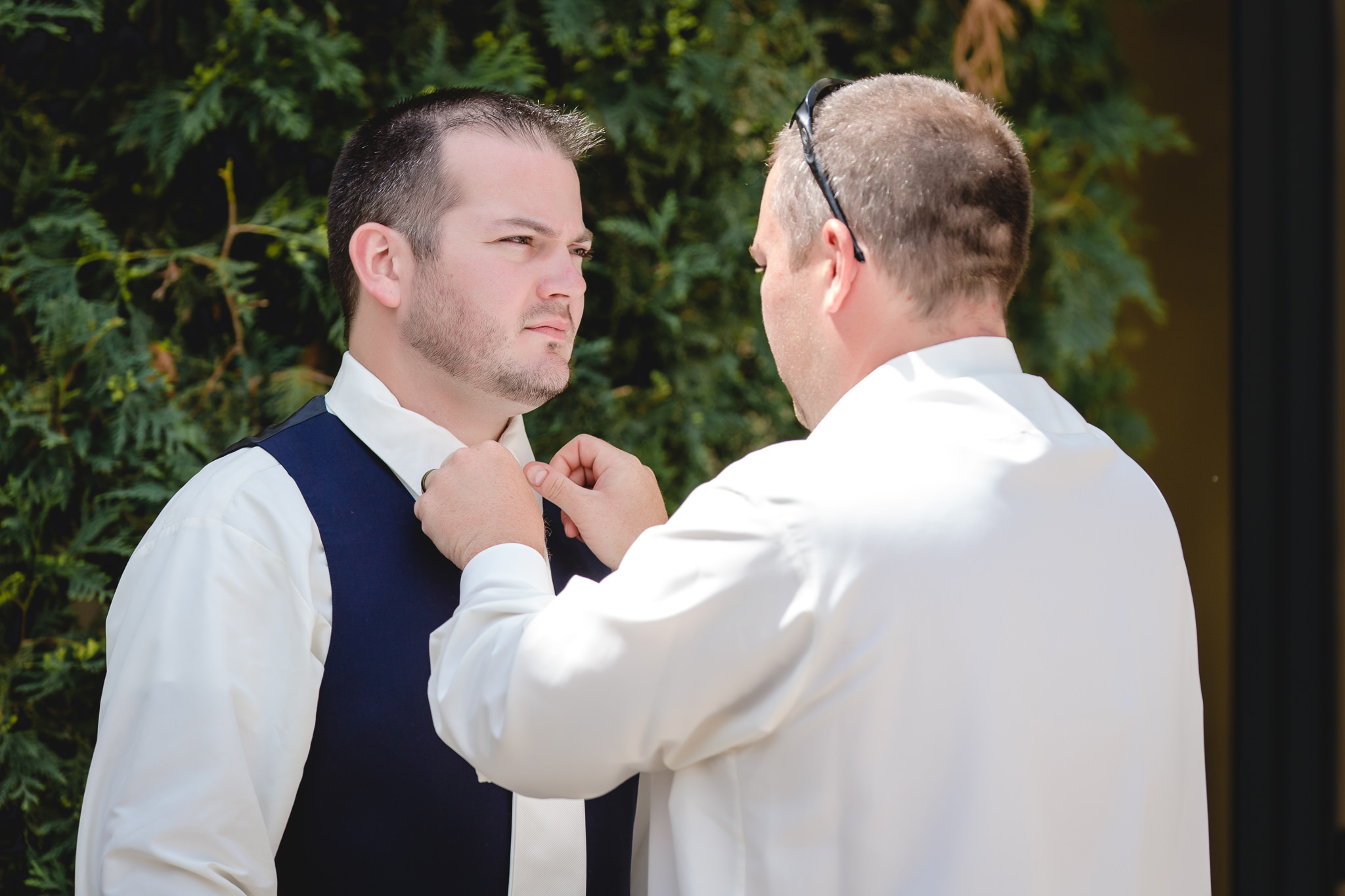 Groom's brother adjusts his tie at the Pittsburgh Airport Marriott