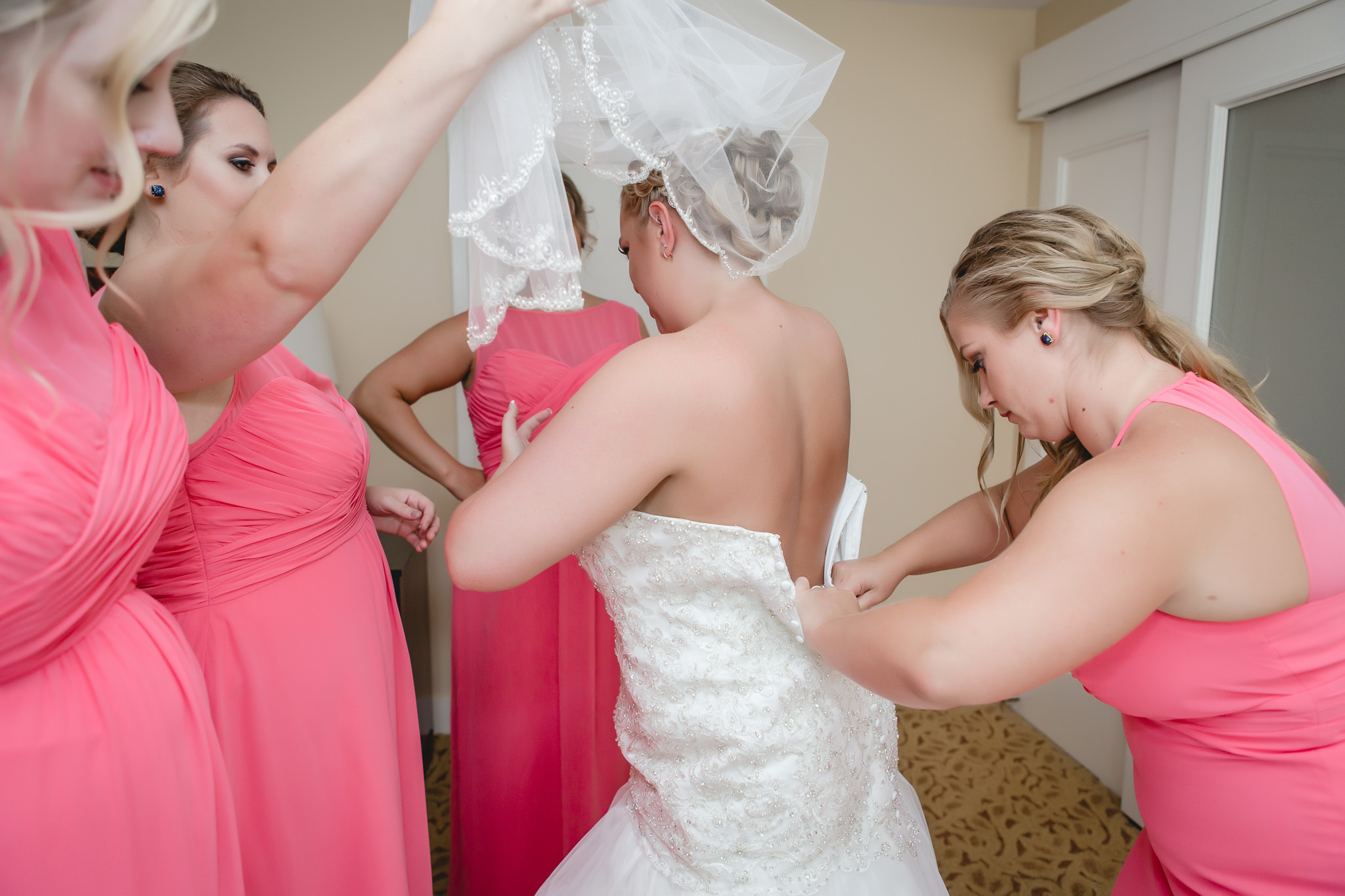 Bridesmaids help the bride into her dress in a suite at the Pittsburgh Airport Marriott