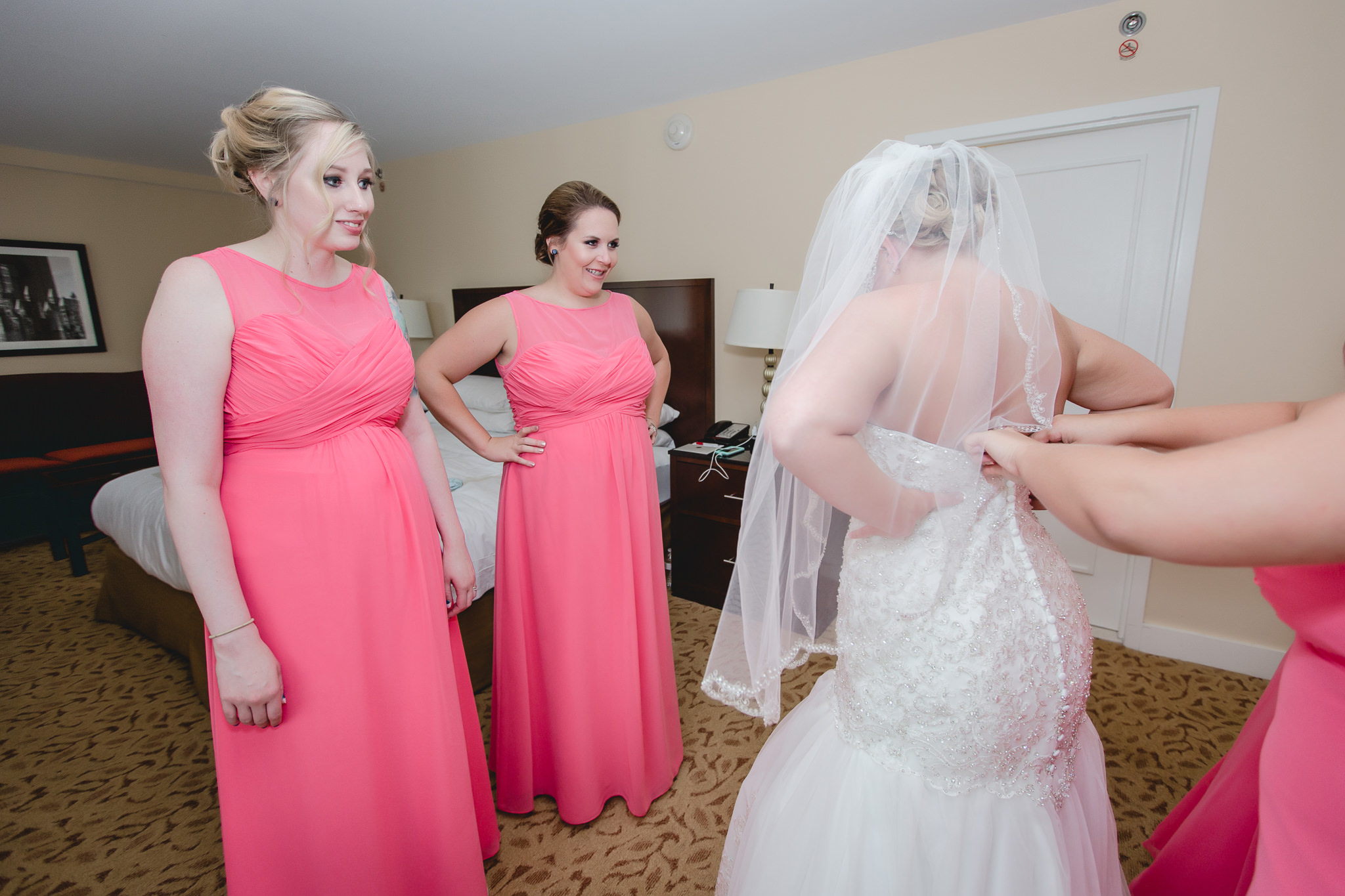 Bridesmaids smile as the bride gets dressed at the Pittsburgh Airport Marriott