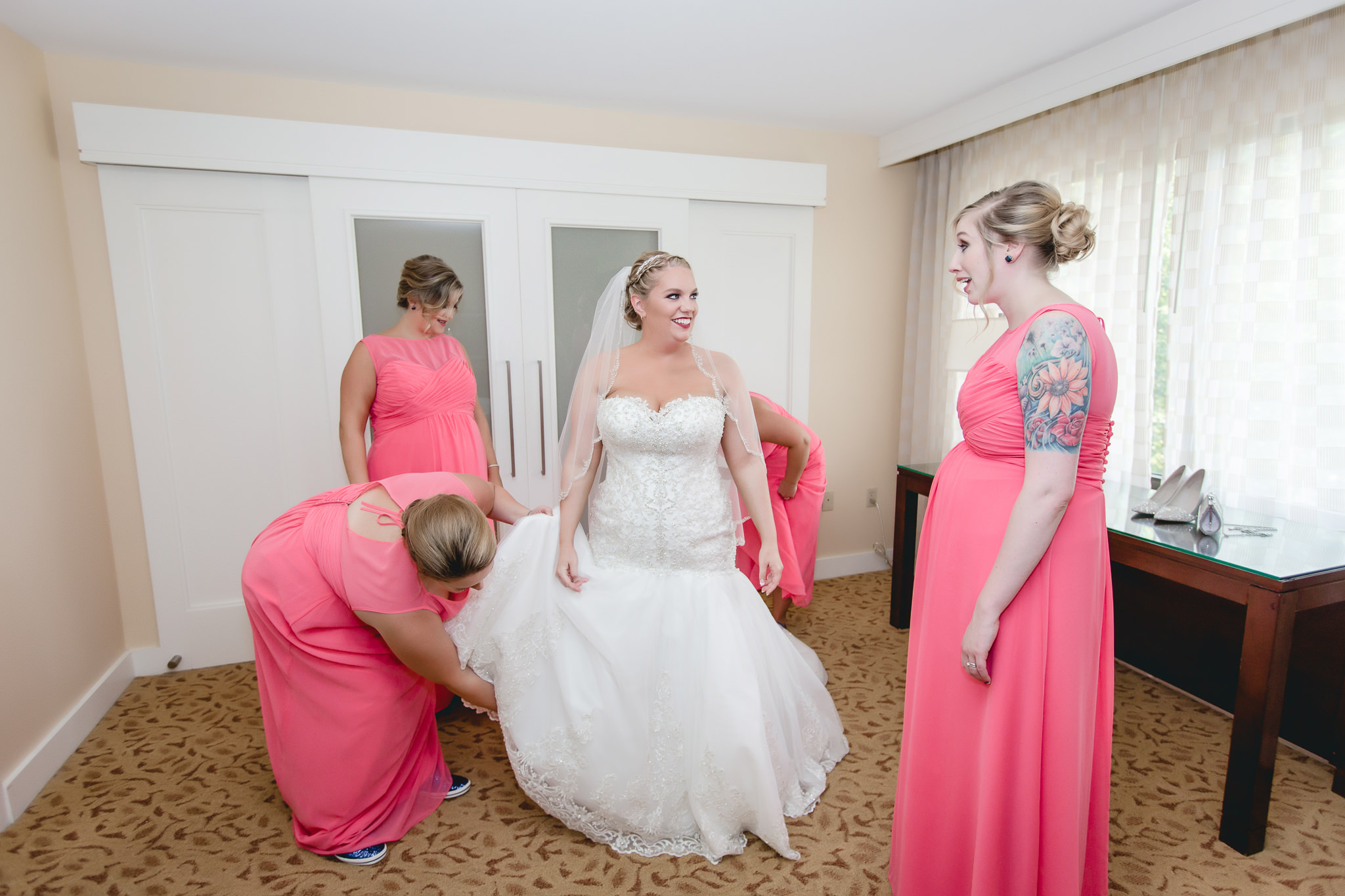 Bride smiles as her bridesmaids help her get dressed for her wedding