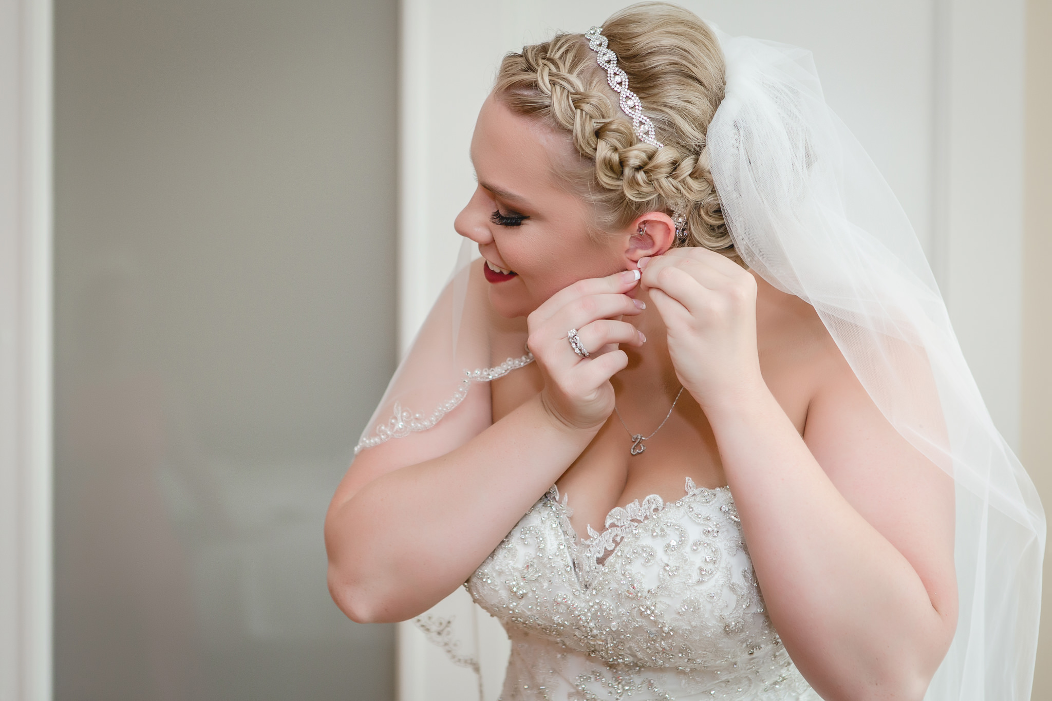 Bride puts on her earrings before her wedding at the Pittsburgh Airport Marriott