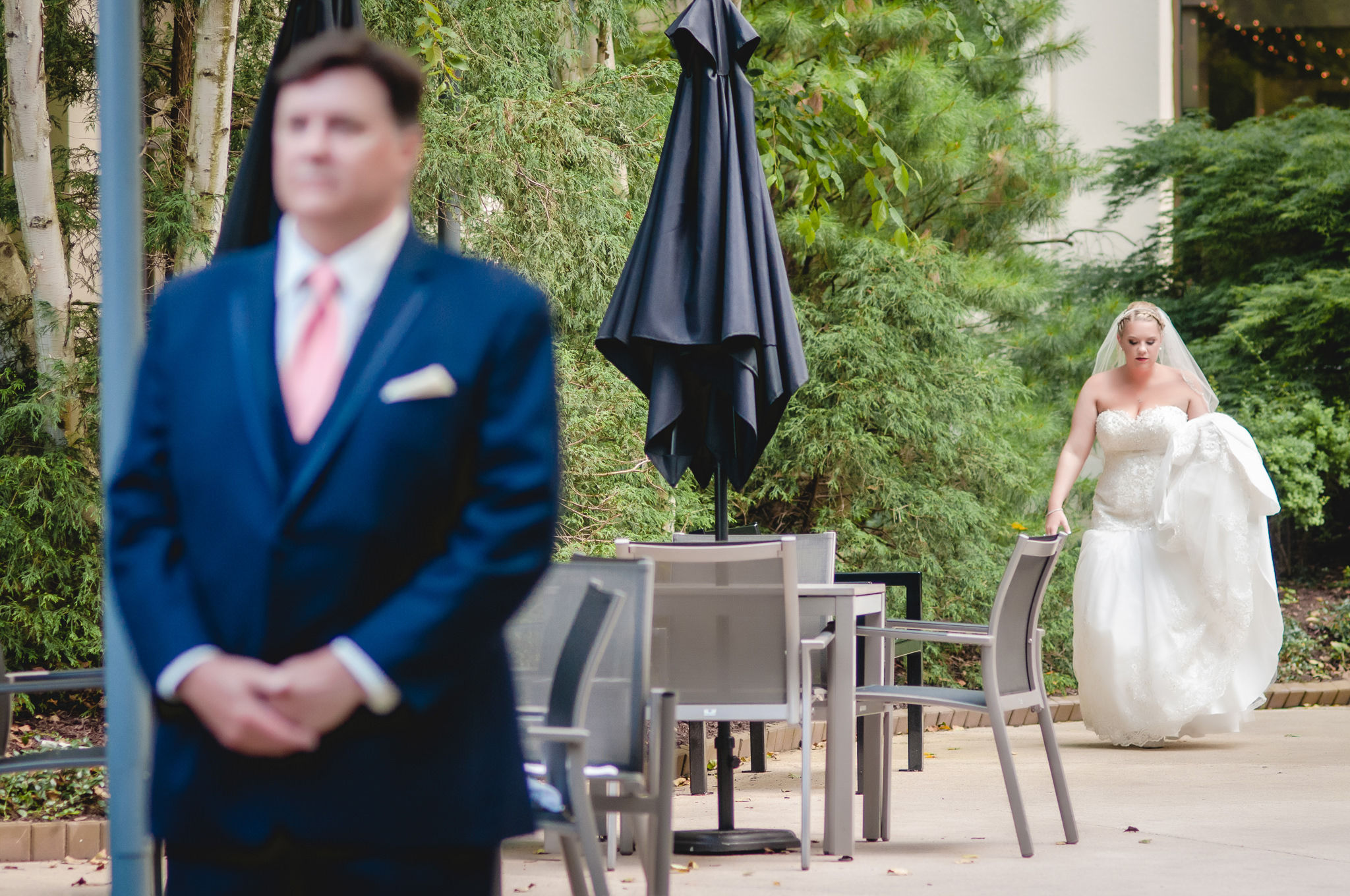 Bride walks towards her dad for a first look in the Pittsburgh Airport Marriott courtyard