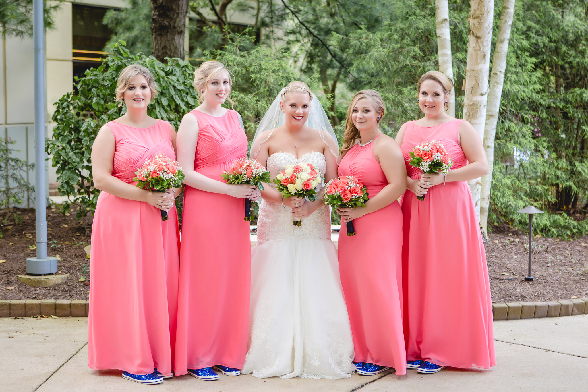 Bride poses with her bridesmaids in their blue sparkly Keds