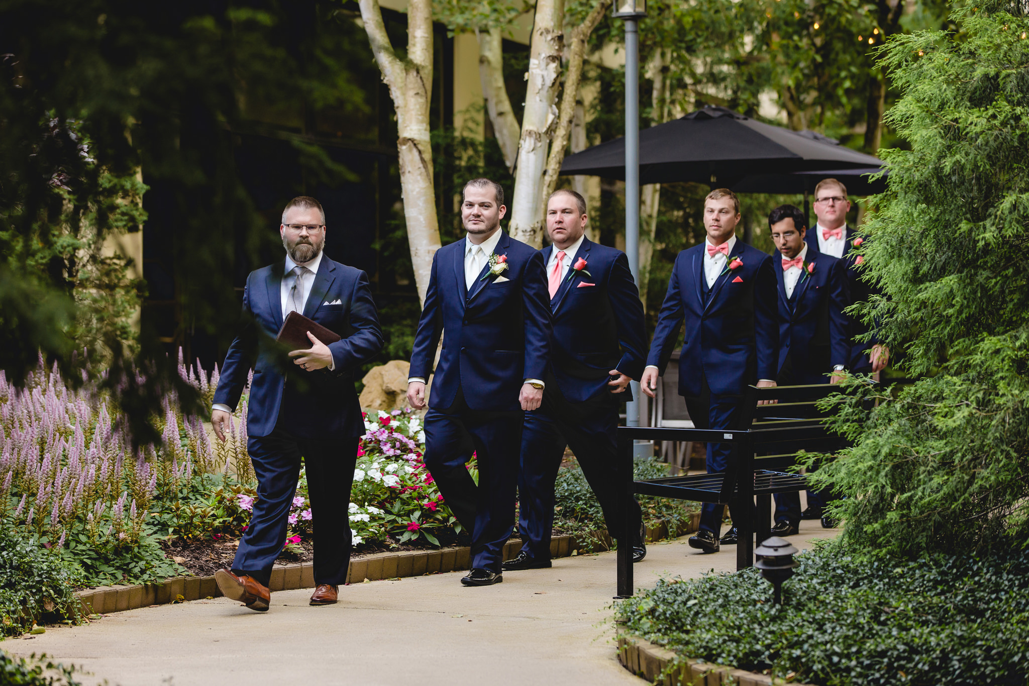 Officiant leads the way as the groom and groomsmen walk to the wedding ceremony