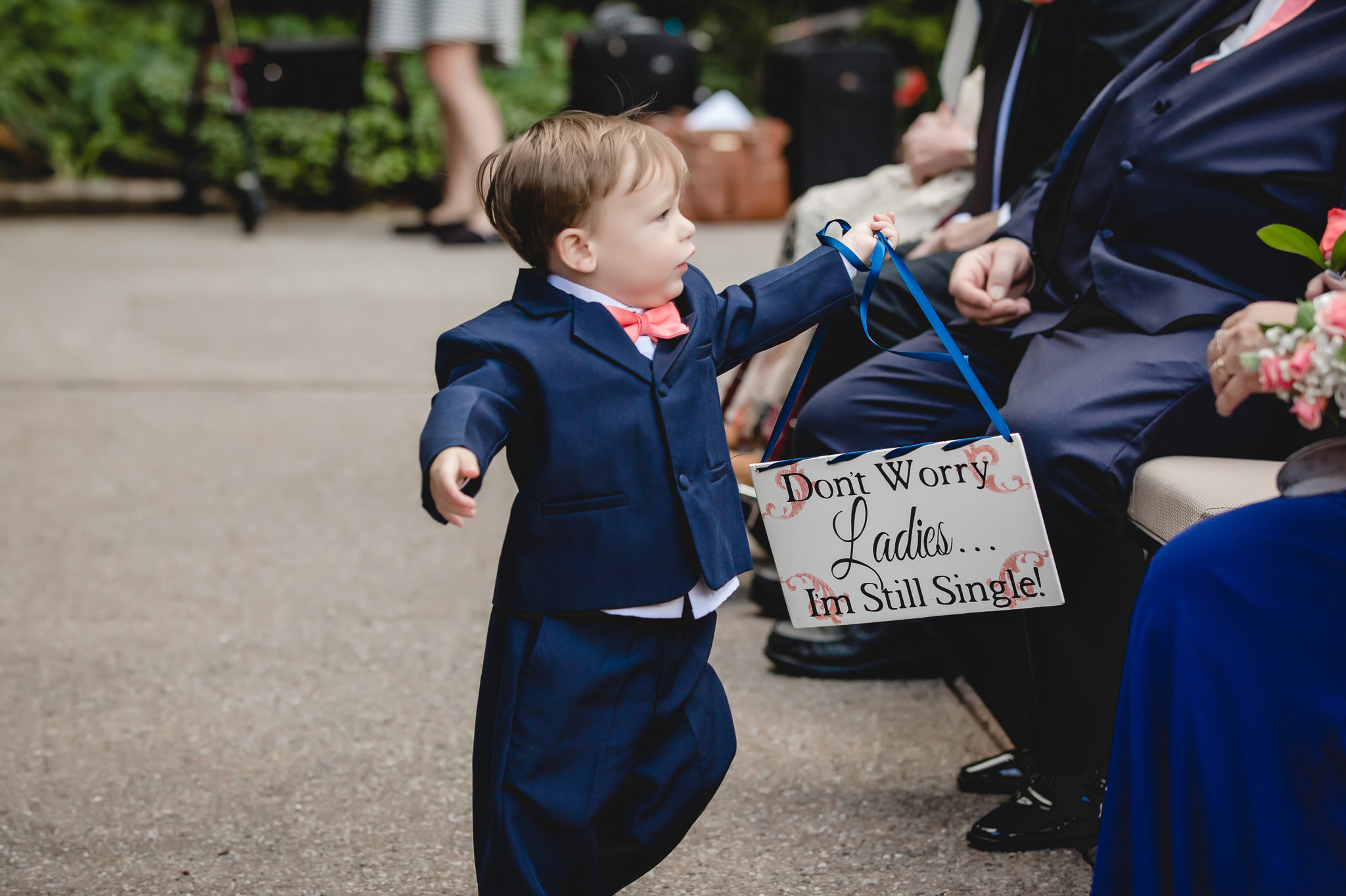 Ring bearer carries a sign during a wedding reception