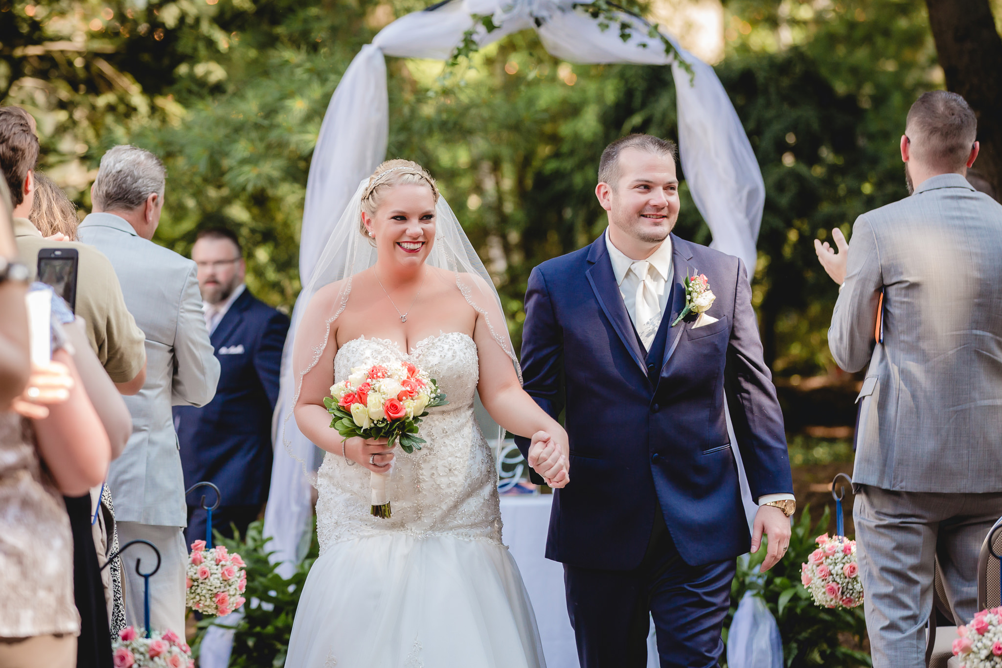Newlyweds recess down the aisle of their courtyard ceremony at Pittsburgh Airport Marriott