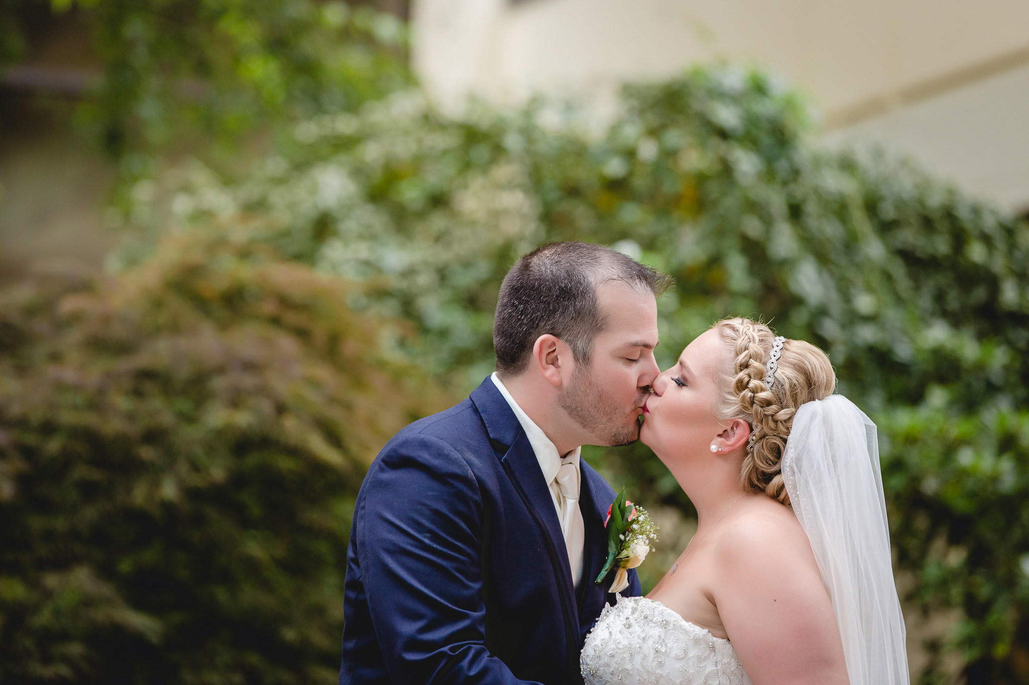 Bride and groom kiss in the courtyard of the Pittsburgh Airport Marriott
