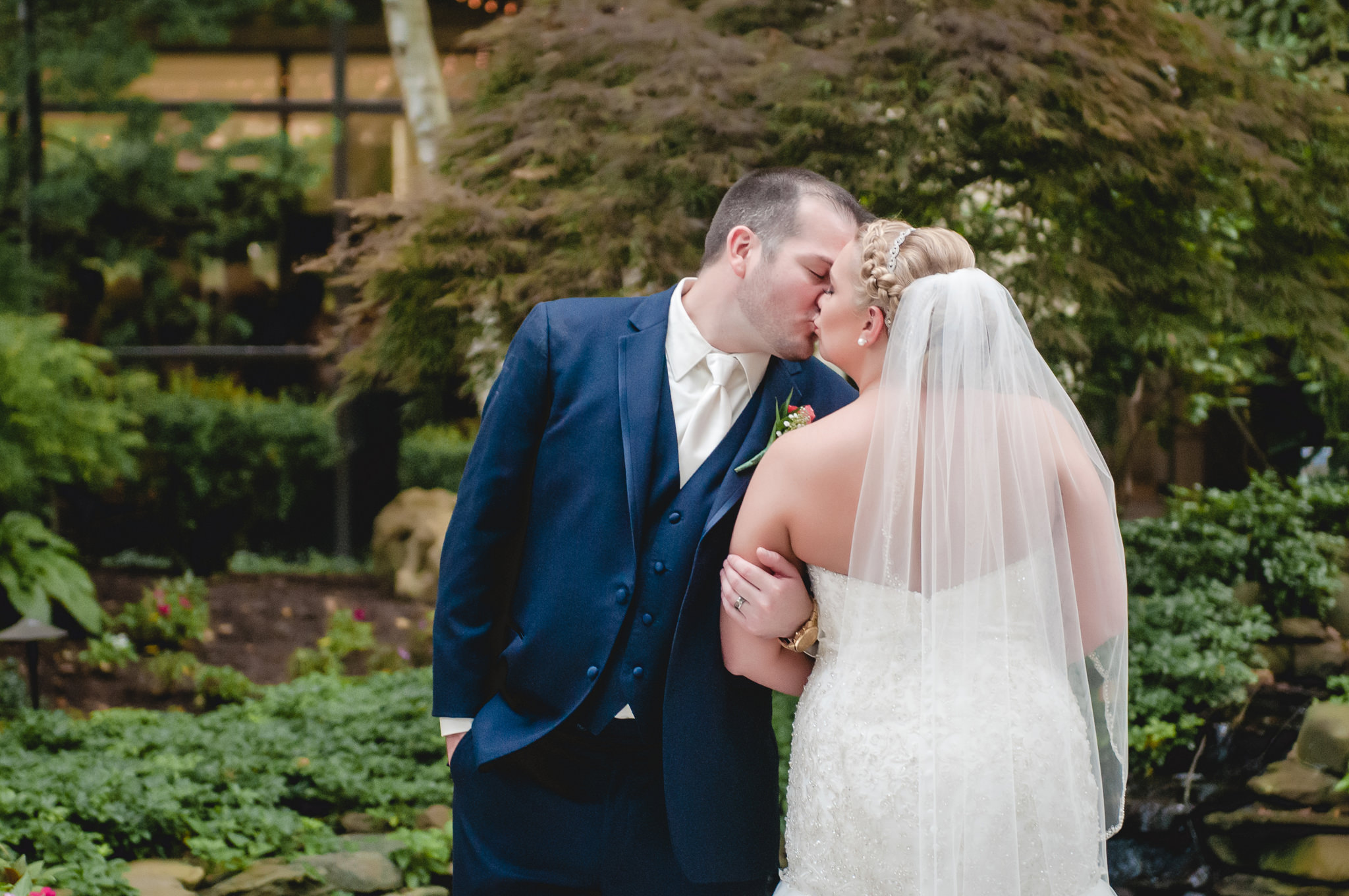 Bride and groom kissing in the Pittsburgh Airport Marriott courtyard