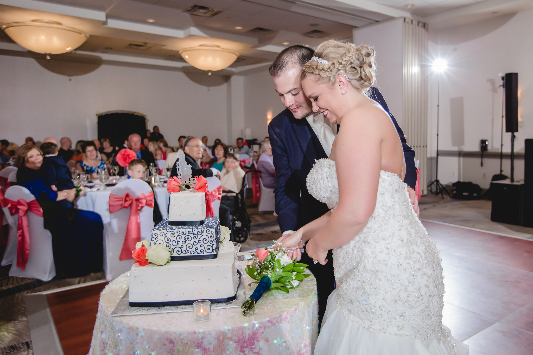 Bride and groom cut the cake in the Three Rivers Room of the Pittsburgh Airport Marriott