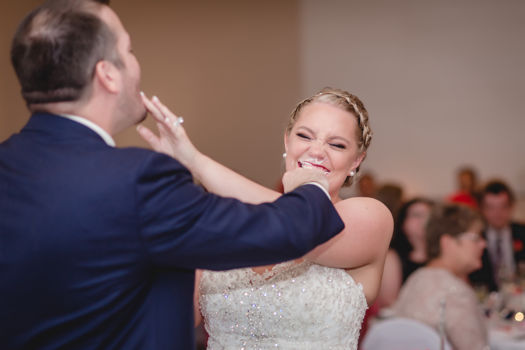 Groom smears icing on the bride's face