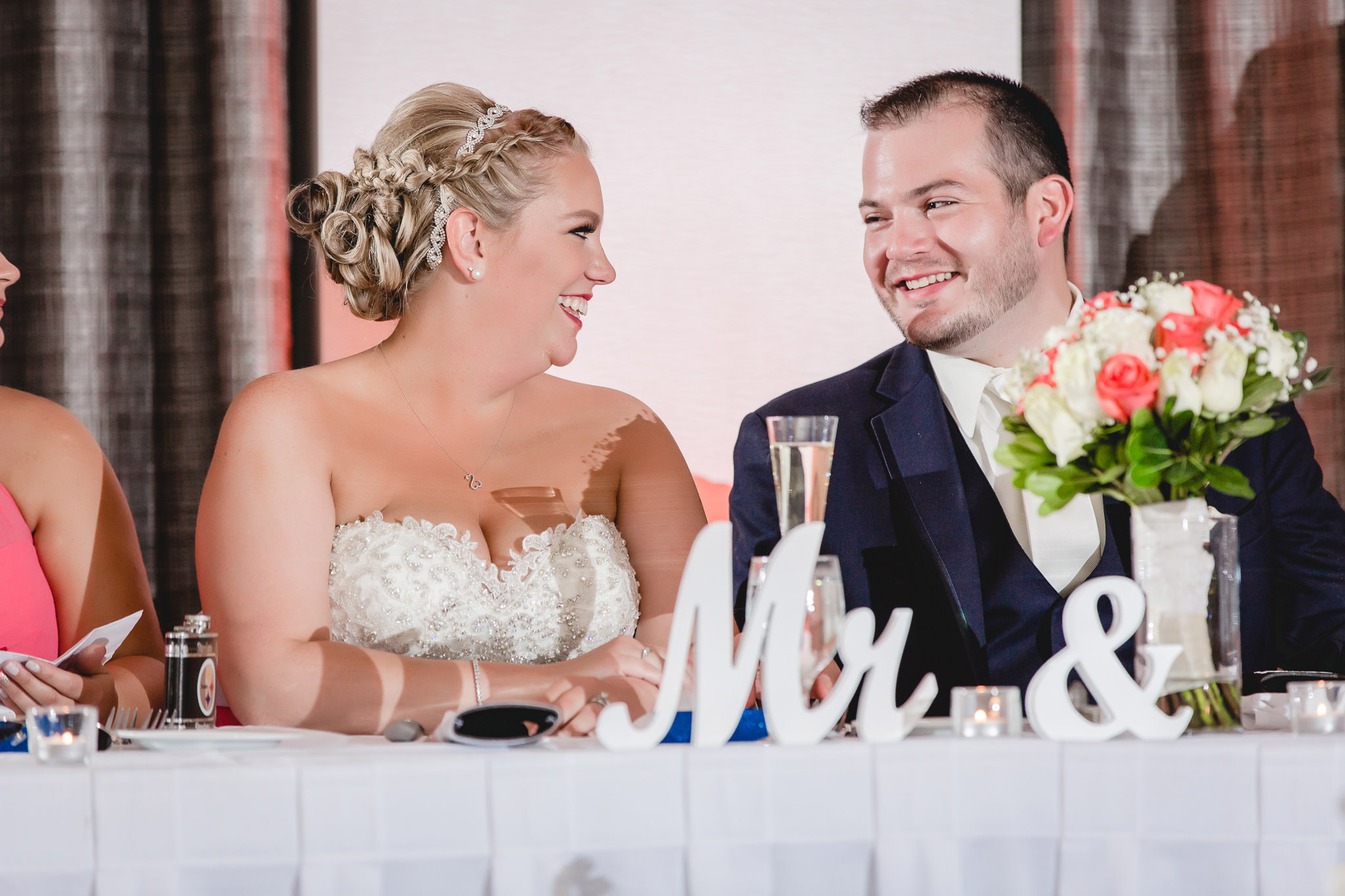 Bride and groom laugh during speeches at the Pittsburgh Airport Marriott