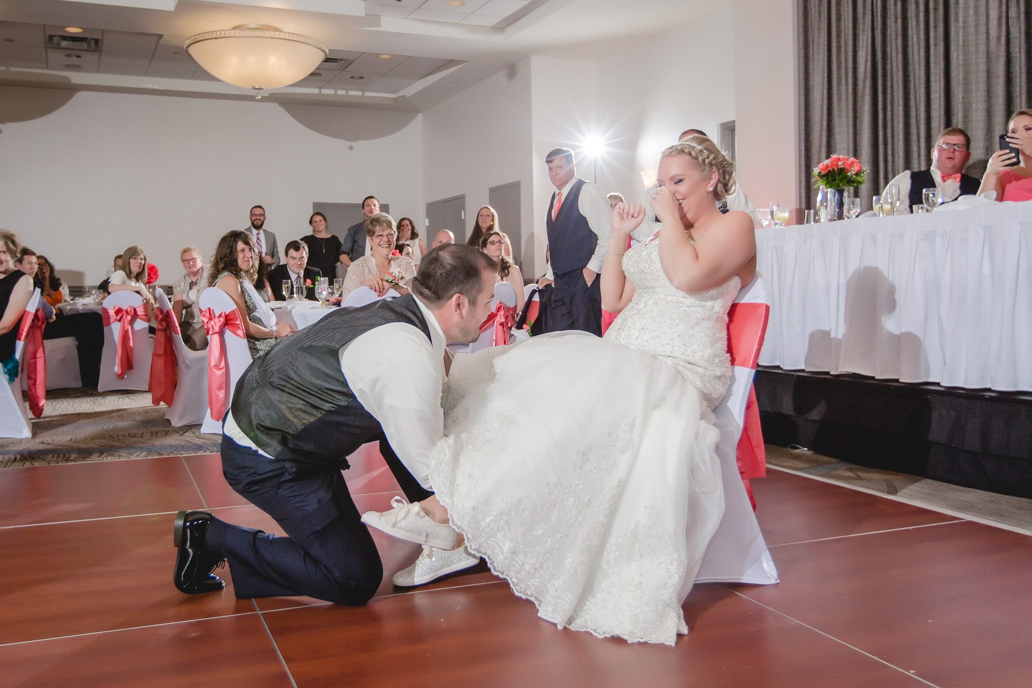 Groom reaches up the bride's dress for her garter