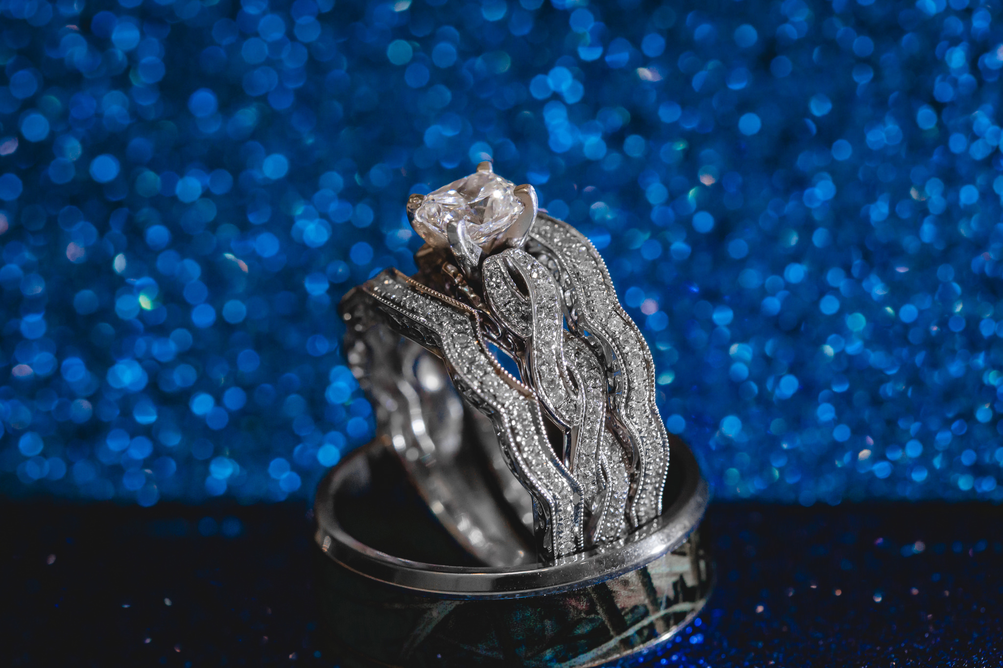 Wedding bands in front of a blue glitter background