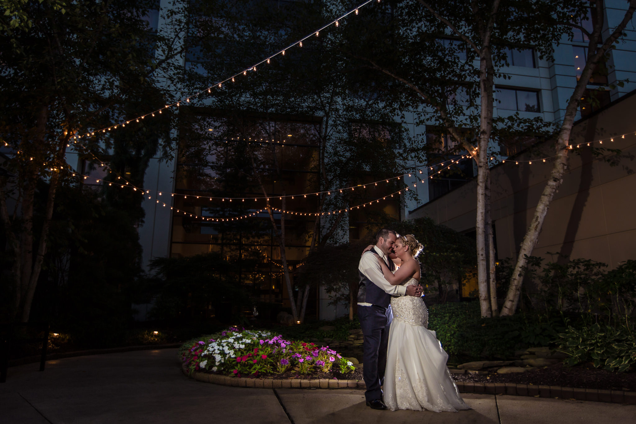 Bride and groom pose at night in the courtyard of the Pittsburgh Airport Marriott